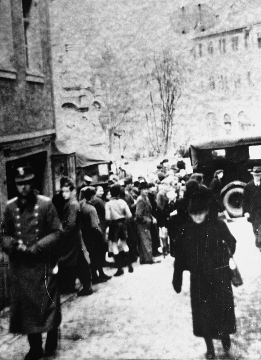 Local residents look on as a group of Jewish deportees arrives at the Fränkischen Hof assembly center during a deportation action in Kitzingen.