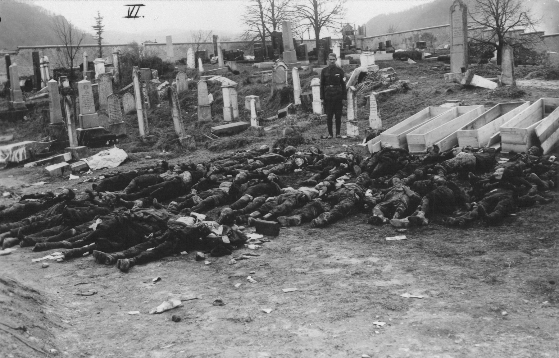 A Soviet guard stands near the corpses exhumed from a mass grave.  The victims will be reburied in coffins in the cemetery.