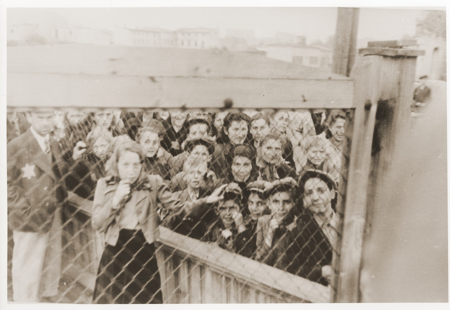 "Women and children who have been selected for deportation, are photographed through the wire fence of the central prison, during the ""Gehsperre"" action in the Lodz ghetto."