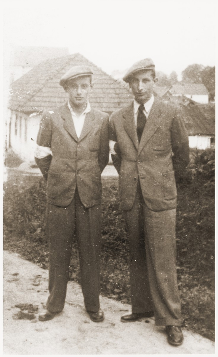 Two Jewish brothers wearing armbands pose outside in the Wisnicz Nowy ghetto.  Pictured are Henryk and Maniek Wiener.
