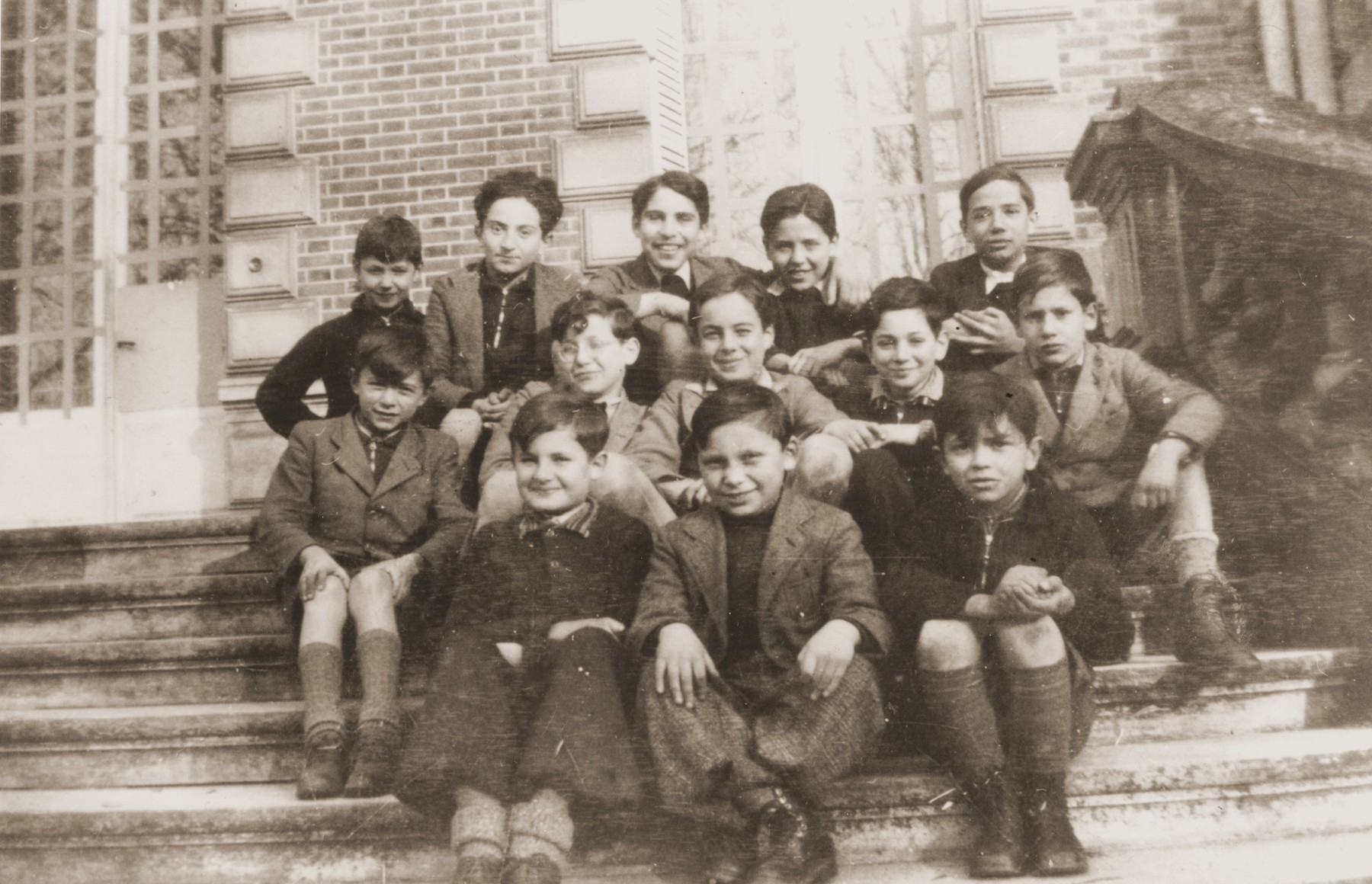 Group portrait of German-Jewish refugee children who were sent to France on a Kindertransport in the spring of 1939 on the steps of the Quincy-sous-Senart children's home near Paris.    Among those pictured are Arno Marcuse (front row, left), Norbert Bikales (second row, left),  Wolfgang Blumenreich (second row, third from left), Gerhard Alexander (second row, second from right), Gerhard Glass (second row, far right), Eric Goldfarb (back row, second from left), Walter Herzig (back row, center), Heinz Stephan Lewy (top row, second from the right) and Gerhard Rosenzweig (top row, far right).