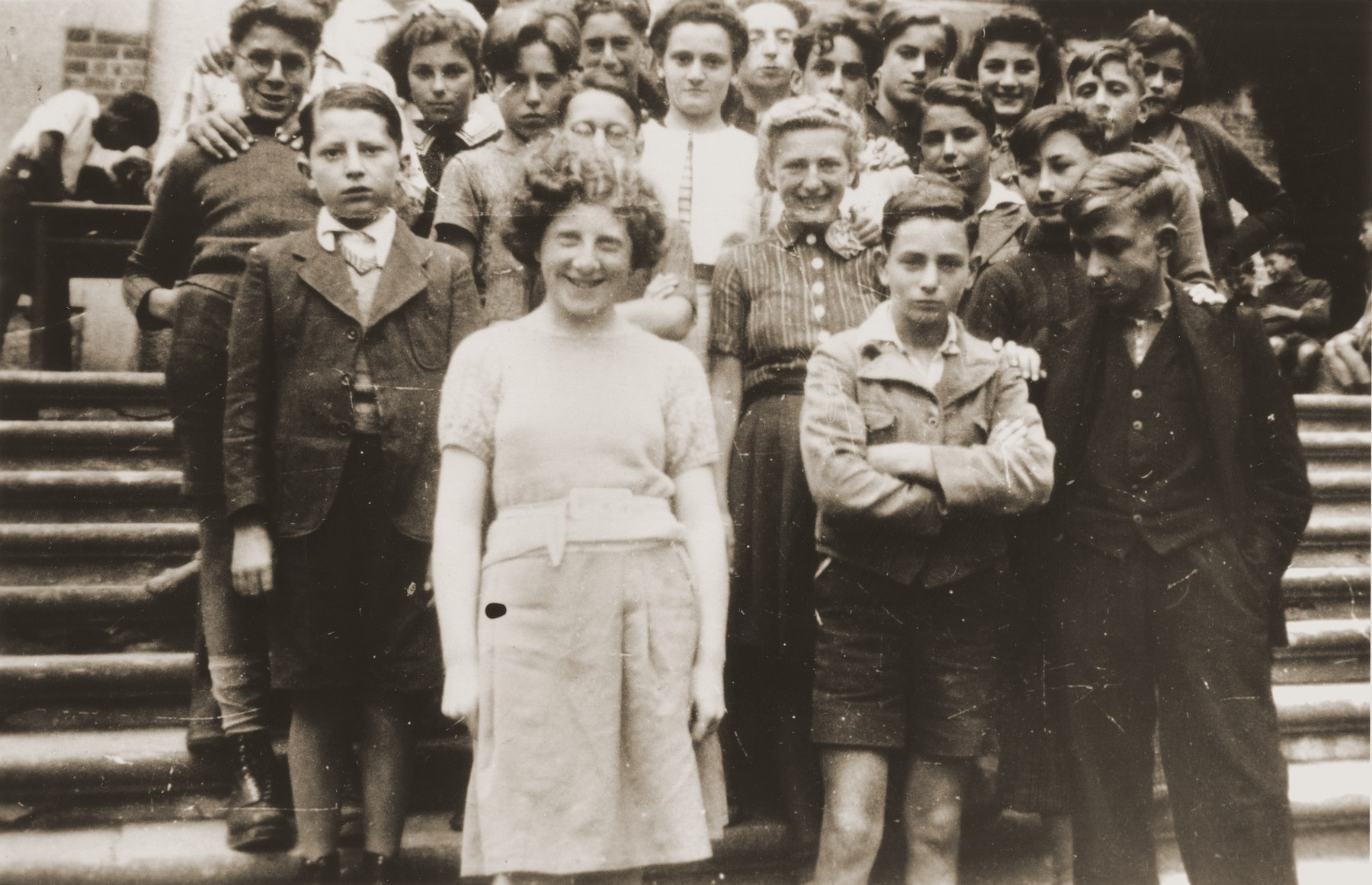 Jewish refugee youth pose on the staircase of the Château de Chabannes children's home near Limoges.  The home was sponsored by the OSE (Oeuvre de secours aux Enfants).    Among those pictured are Heinz Stephan Lewy (third row, second from the left); Gerard Alexander (front row, center); Armand Chochenbaum (back row, far left); Ruth Adwokat (back row, second from the left), and  Siegfried Knop (back row, center)..