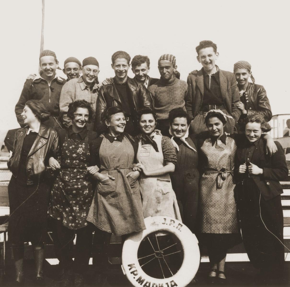 Group portrait of members of the Hashomer Hatzair Zionist youth aboard one of the riverboats (the Kraljica Marija) of the Kladovo transport.  Pictured in the top row from left to right are Zeev Kulka, Josef Cohen, Dov Eshel, Erich Nachhaeuser, Max Stricker, Yehezkel Tanenbaum, Arieh Erez and Avi Marienberg.  In the front row are Margalit Figer, Yael Pagi, Batya Horovitz, Ruth Galilee, Shoshana Dukes, Hannah Rosenwasser and Miriam Pick.