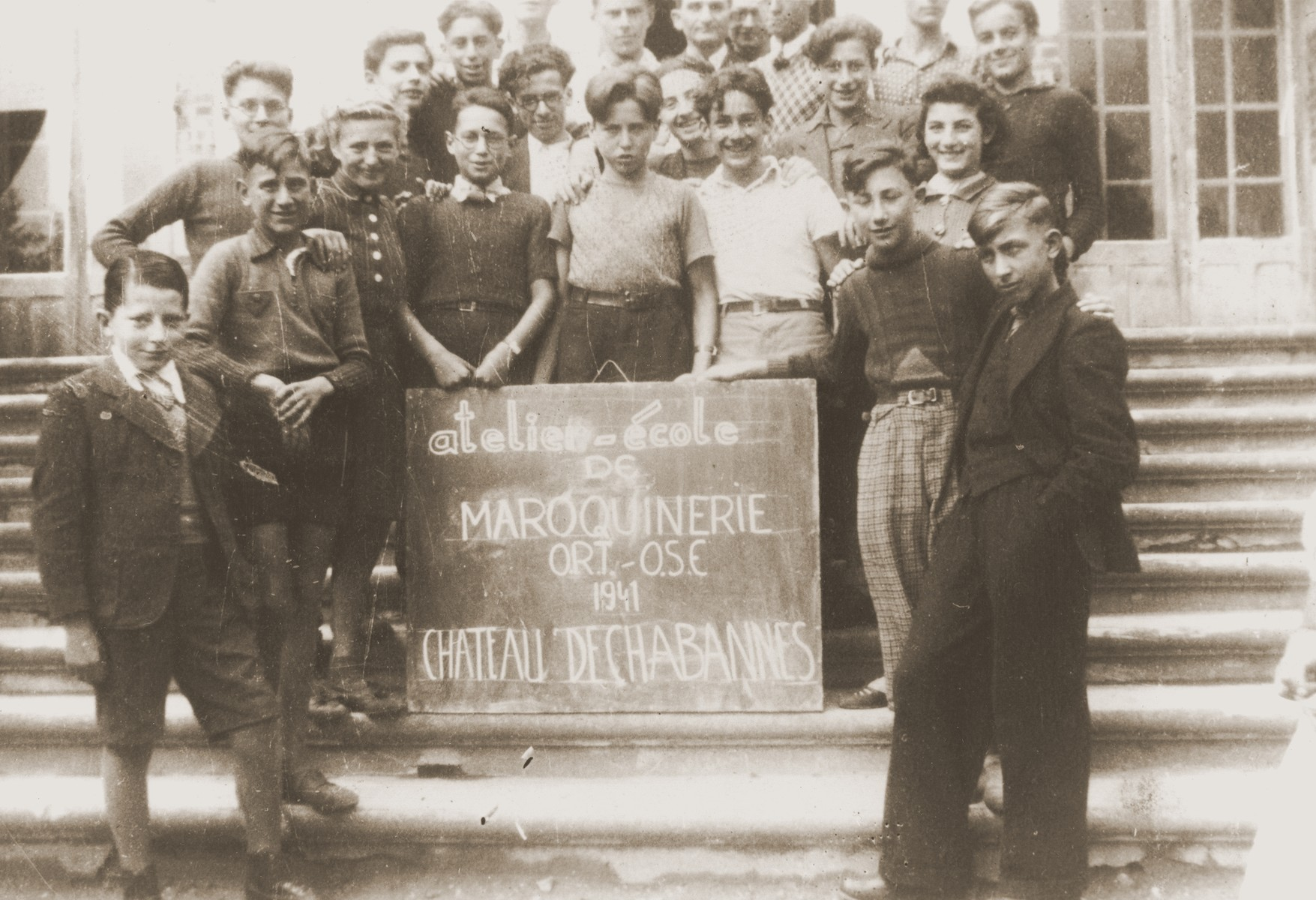 Jewish refugee youth who are students in an ORT leather working class at the Château de Chabannes children's home, pose on the front staircase of the home.  Château de Chabannes was sponsored by the OSE (Oeuvre de secours aux Enfants).    Heinz Stephan Lewy is pictured in the front row, center.  Egon Halbright (born Halbreich) is located in the second row, wearing glasses and a white shirt--identified by his daughter, Rita Halbright