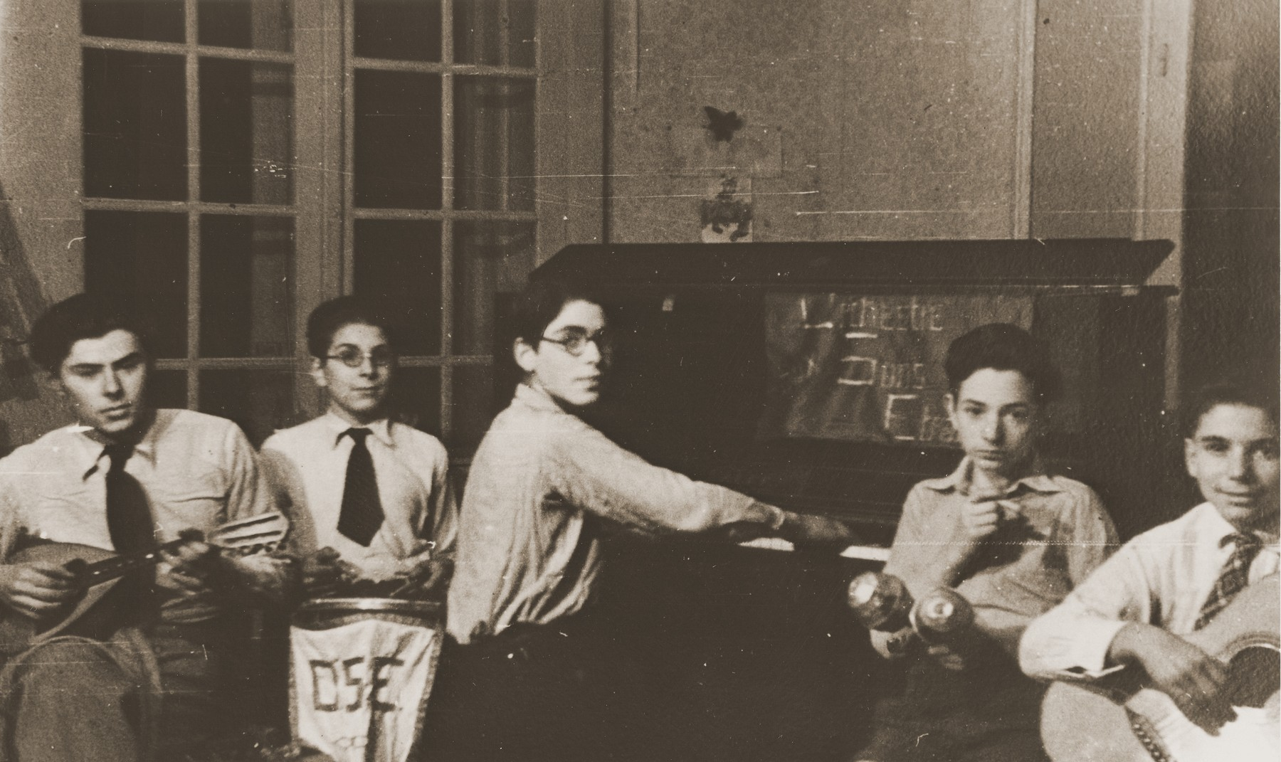 Members of a youth orchestra perform at the Château de Chabannes children's home.  The home was sponsored by the OSE (Oeuvre de secours aux Enfants).  Pictured from left to right are Marjan Szturm, Armand Chochenbaum, Walter Herzig, Gérard Alexander and Peter Marcuse.