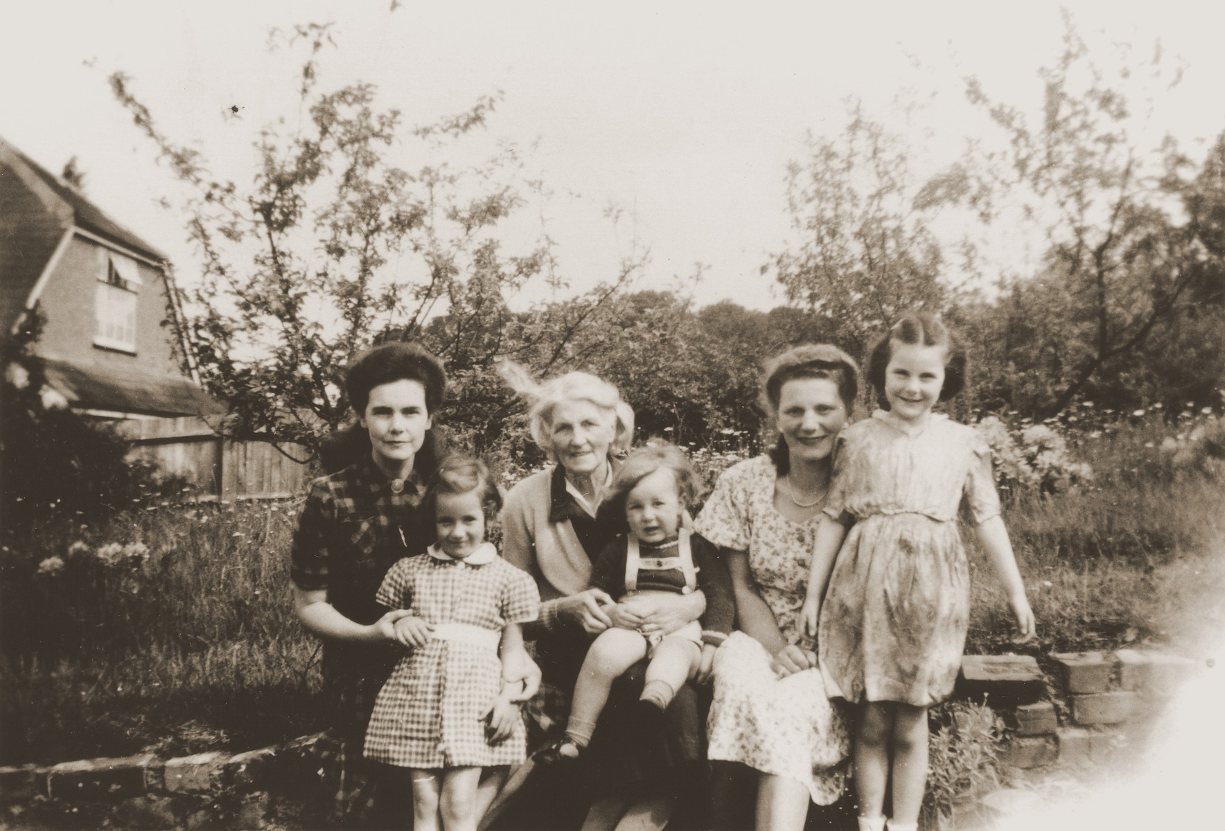 Austrian Jewish refugee Kathe Spiegler (second from the right) poses with the British family who hired her to be a nanny.