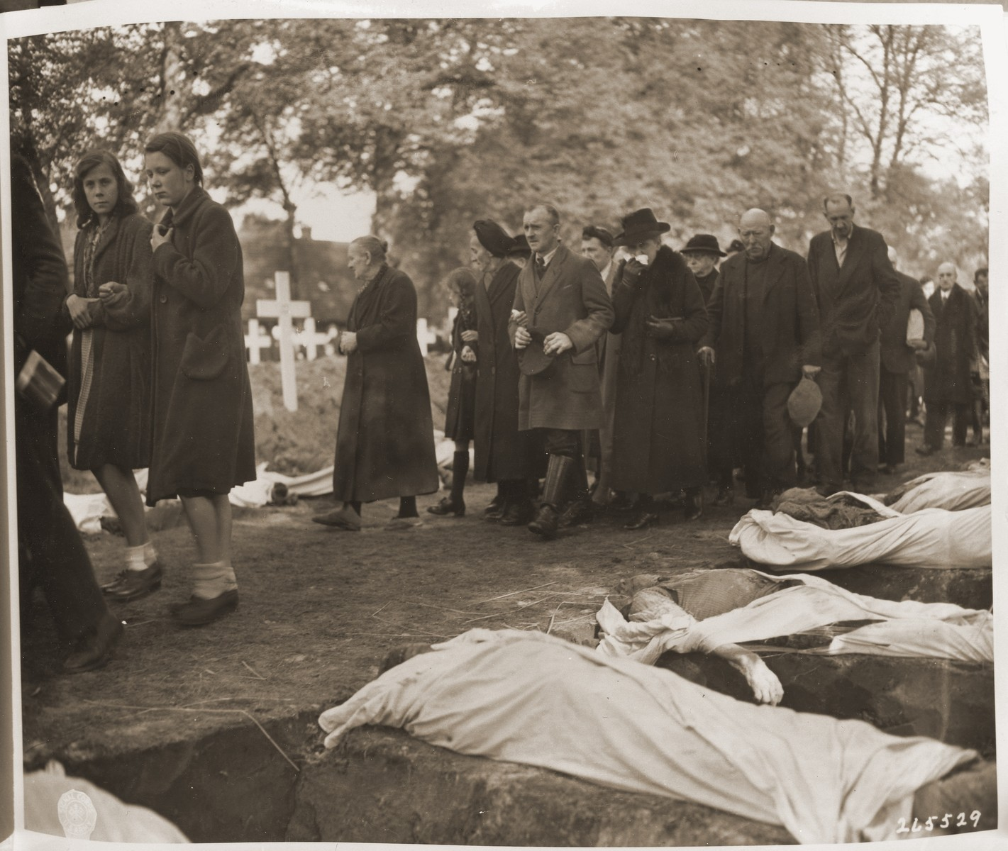 Civilians of all ages are forced to march past the open graves of prisoners from the concentration camp at Woebbelin.  The townspeople were forced by U.S. troops to bury the corpses on the palace grounds of the Archduke of Mecklenburg.