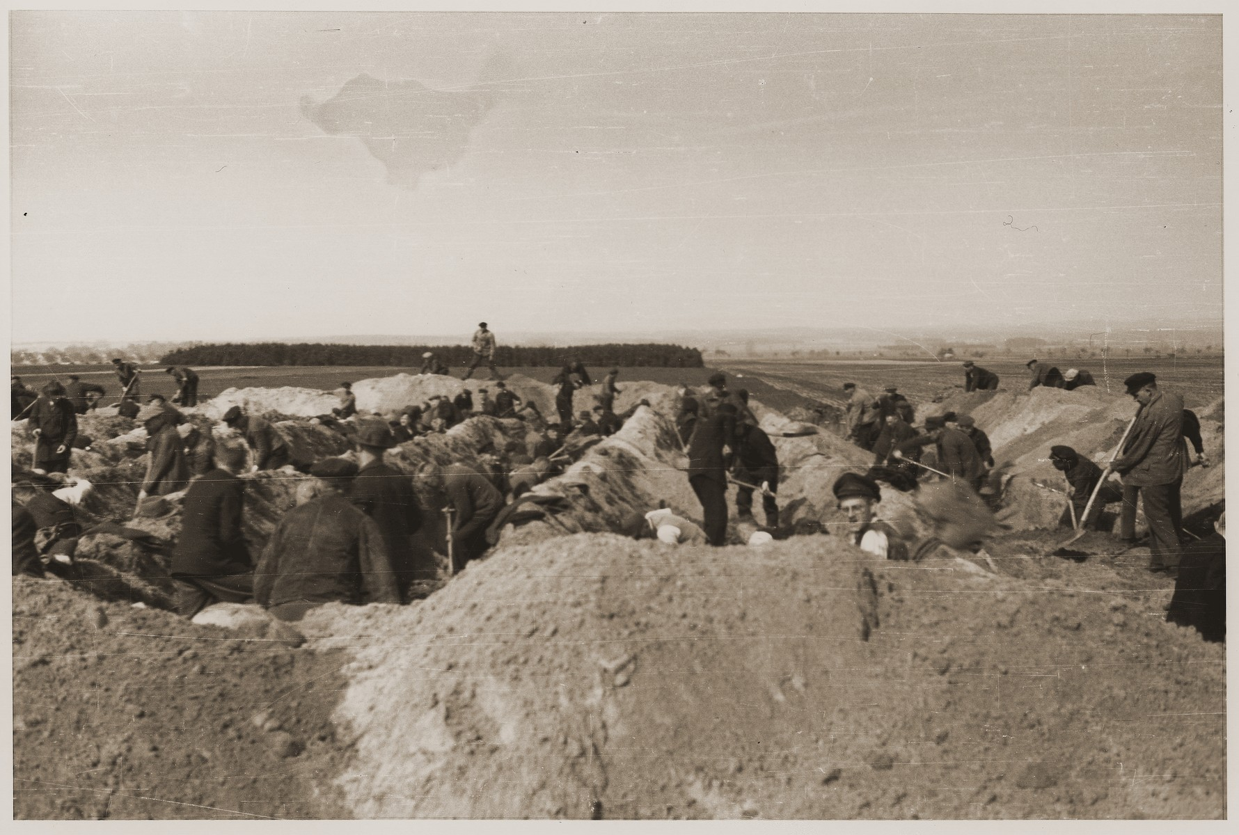 German civilians dig graves for the bodies of concentration camp prisoners killed by the SS in a barn just outside of Gardelegen.