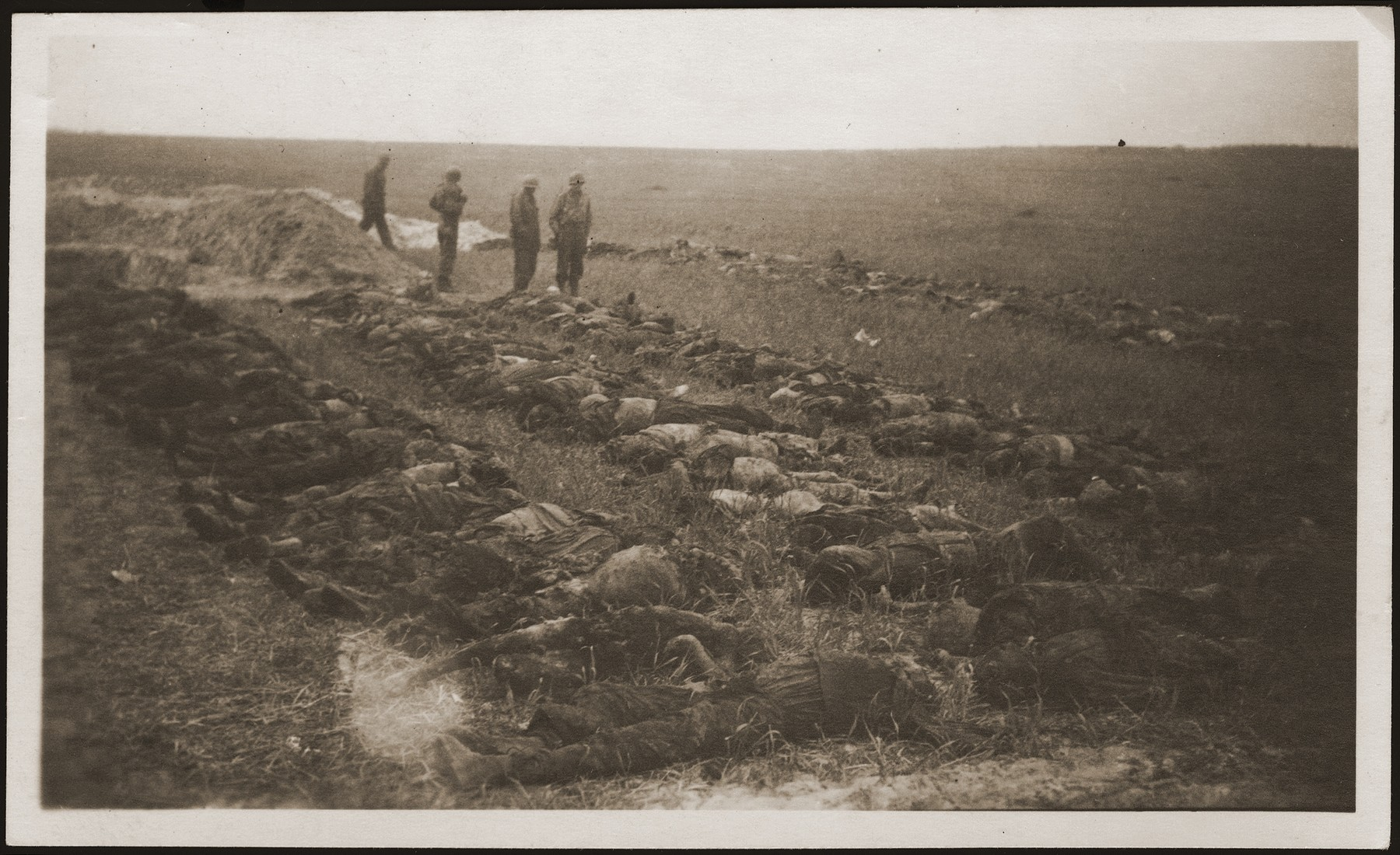 American soldiers stand among the corpses of concentration camp prisoners killed by the SS in a barn just outside of Gardelegen, which have been laid out for burial.