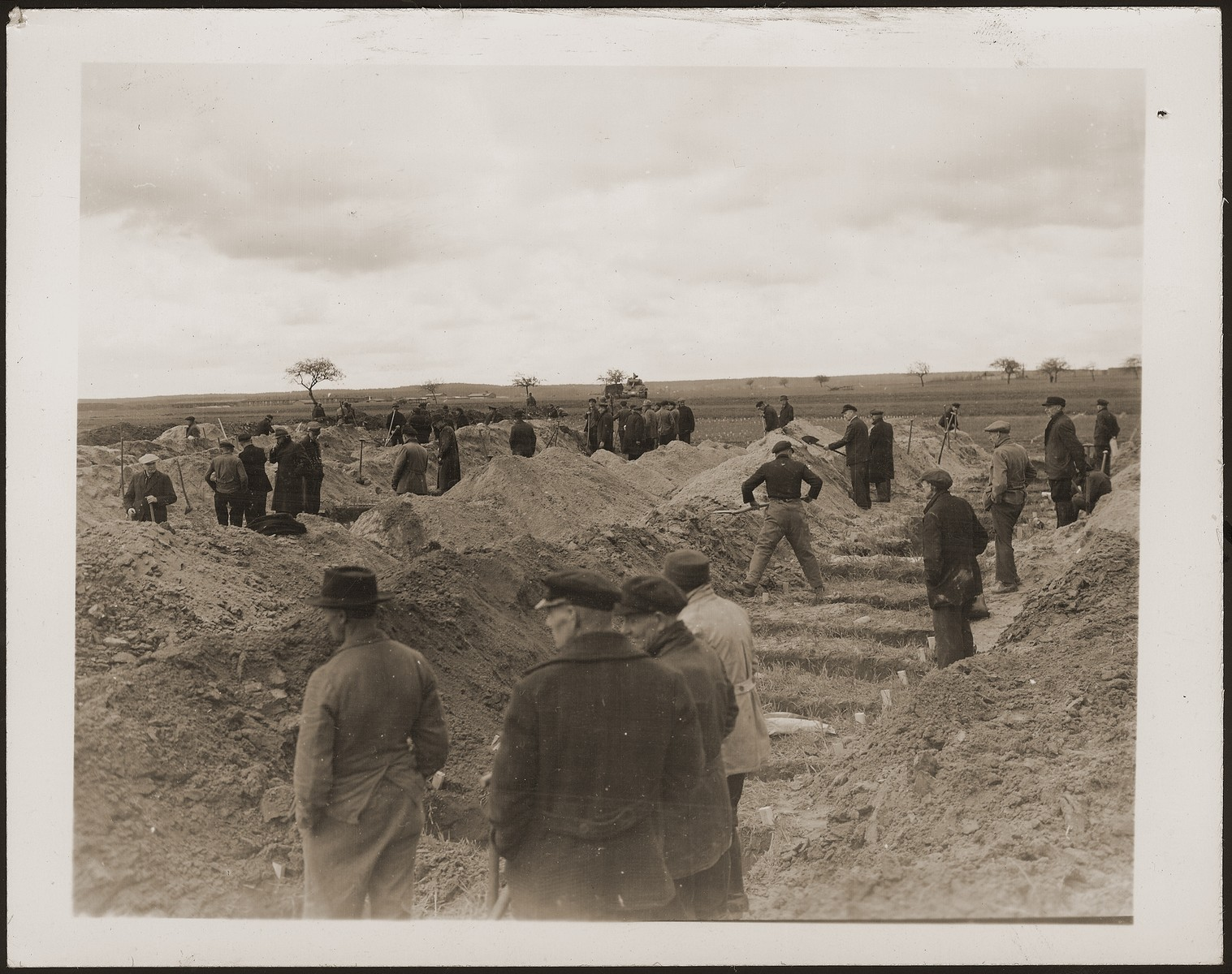 German civilians dig graves for concentration camp prisoners killed by the SS in a barn just outside Gardelegen.