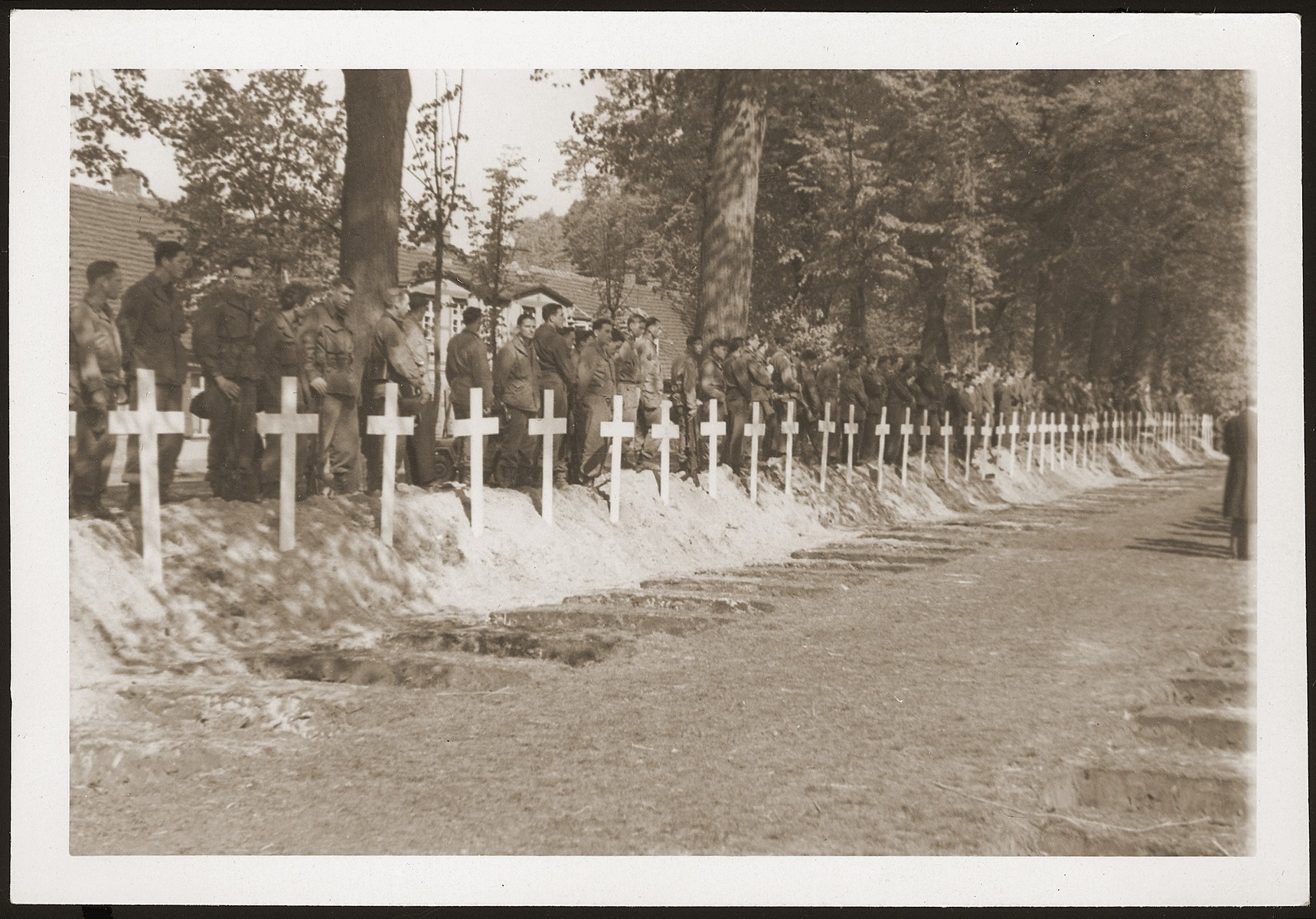 American soldiers stand behind a row of graves at the mass funeral in Ludwigslust on the palace grounds of the Archduke of Mecklenburg, where they forced the townspeople to bury the bodies of prisoners killed in the Woebbelin concentration camp.
