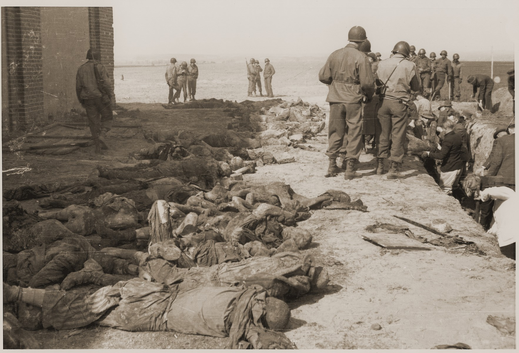 Under the supervision of American soldiers, German civilians exhume the bodies of prisoners killed by the SS in a barn just outside of Gardelegen.