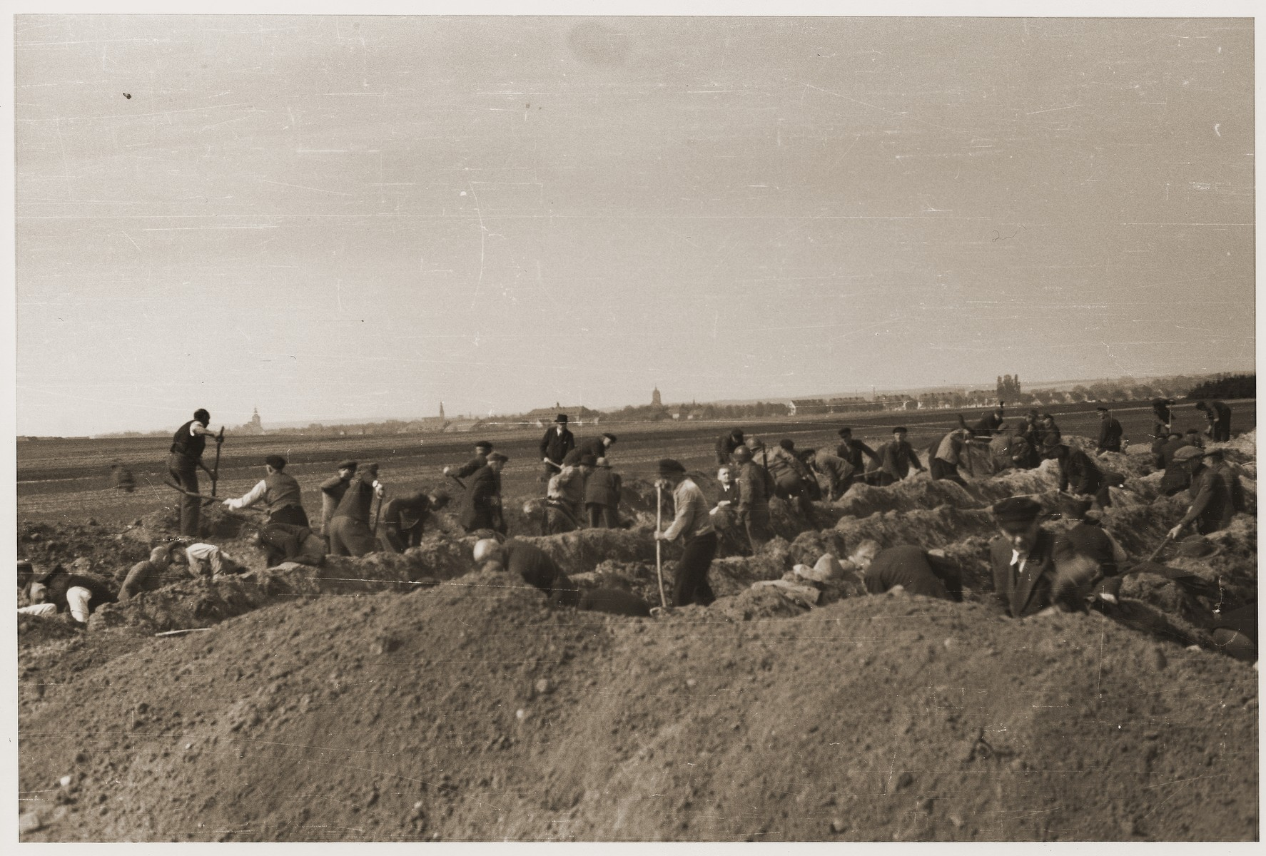 German civilians dig graves for the bodies of concentration camp prisoners killed by the SS in a barn just outside of Gardelegen, which can be seen in the background.