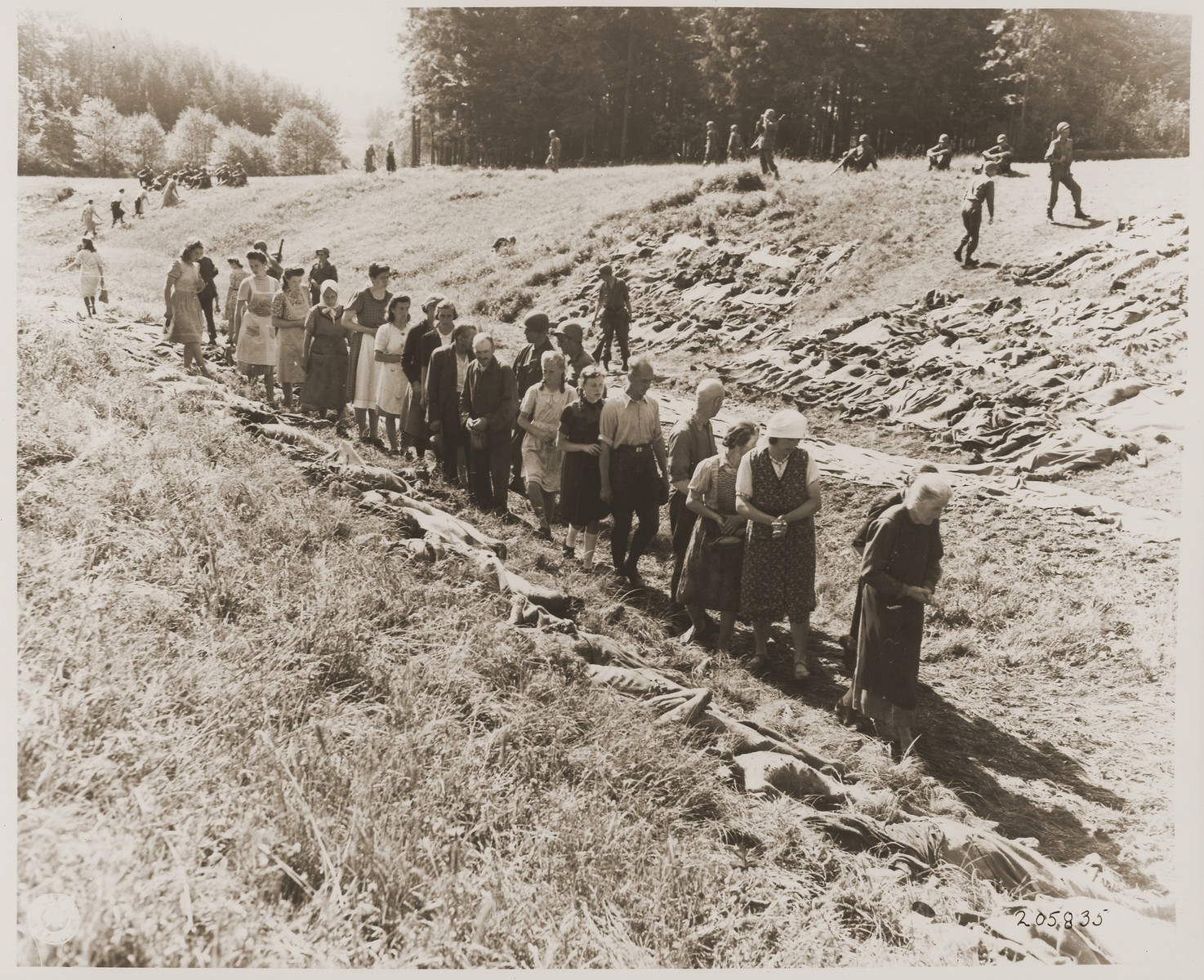 Under the supervision of American soldiers, German civilians from Nammering walk among the corpses of prisoners exhumed from a mass grave near the town.