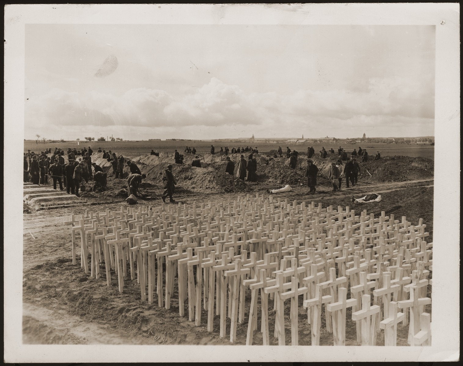 Under the supervision of American soldiers, German civilians dig graves for the bodies of concentration camp prisoners killed by the SS in a barn just outside of Gardelegen.  In the foreground are grave markers that will be placed on the graves.