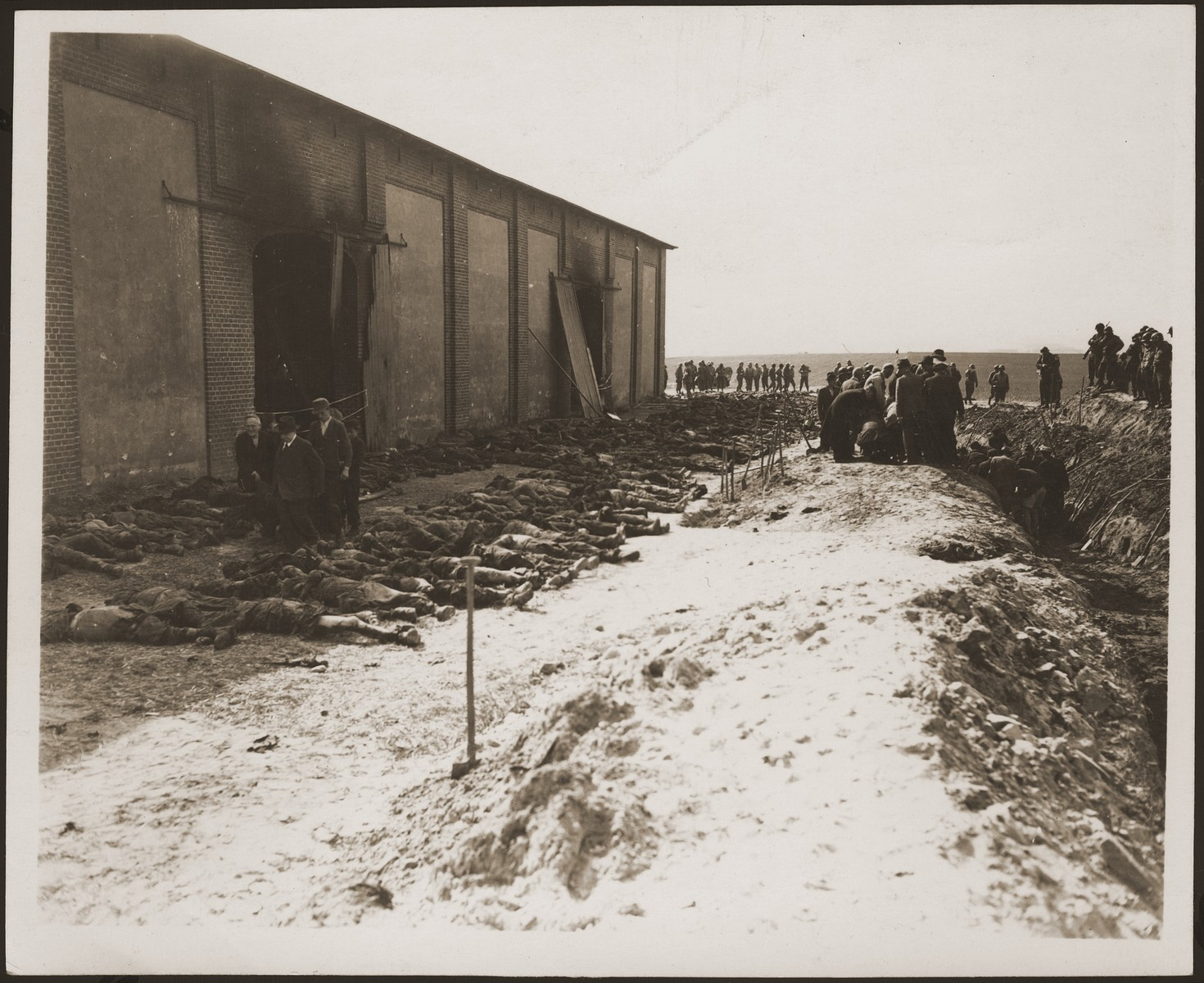 Under the supervision of American soldiers, German civilians exhume the corpses of prisoners killed in a barn and buried in a mass grave by the SS.