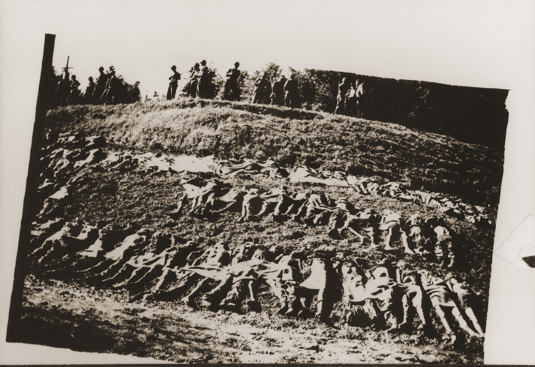 Amercian soldiers stand on the edge of a ravine above the corpses of prisoners exhumed from a mass grave near Nammering.