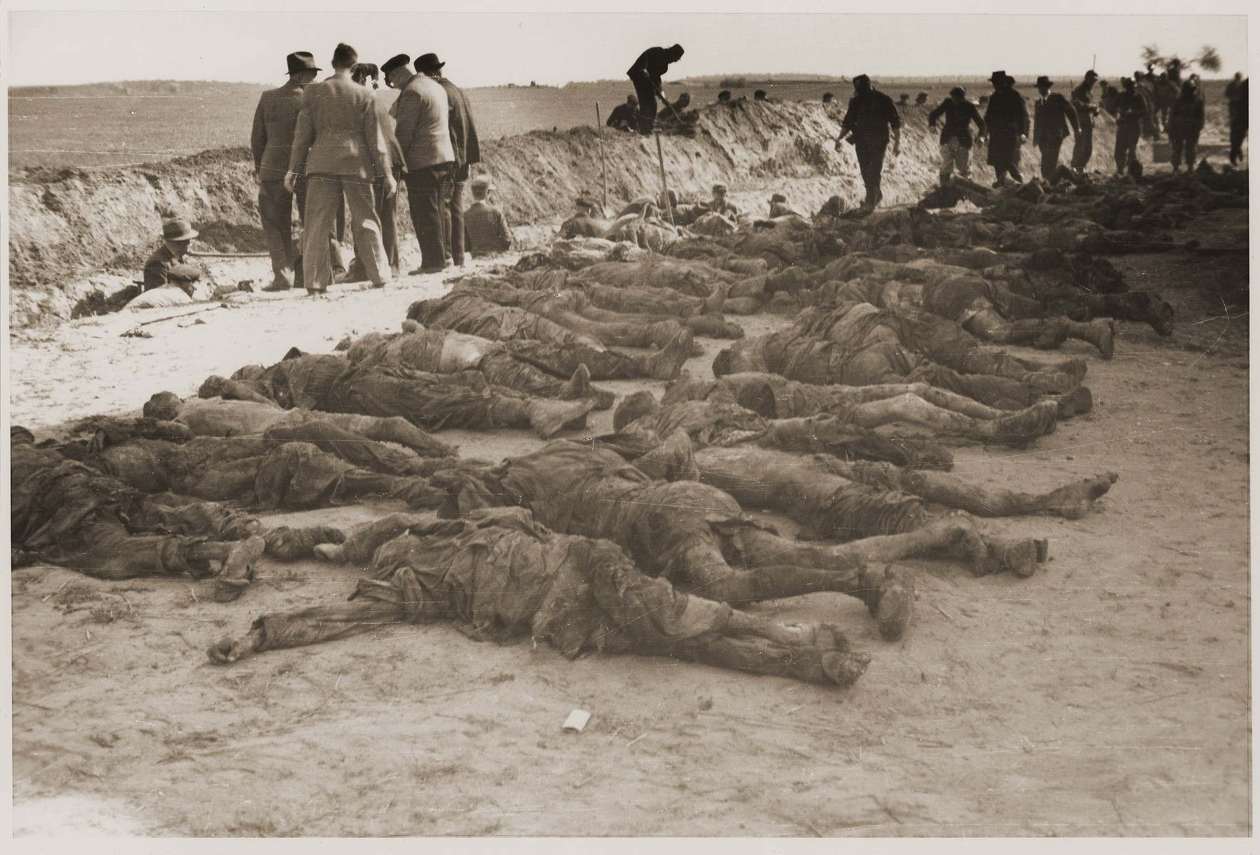Under the supervision of American soldiers, German civilians exhume the bodies of concentration camp prisoners killed by the SS in a barn just outside of Gardelegen.