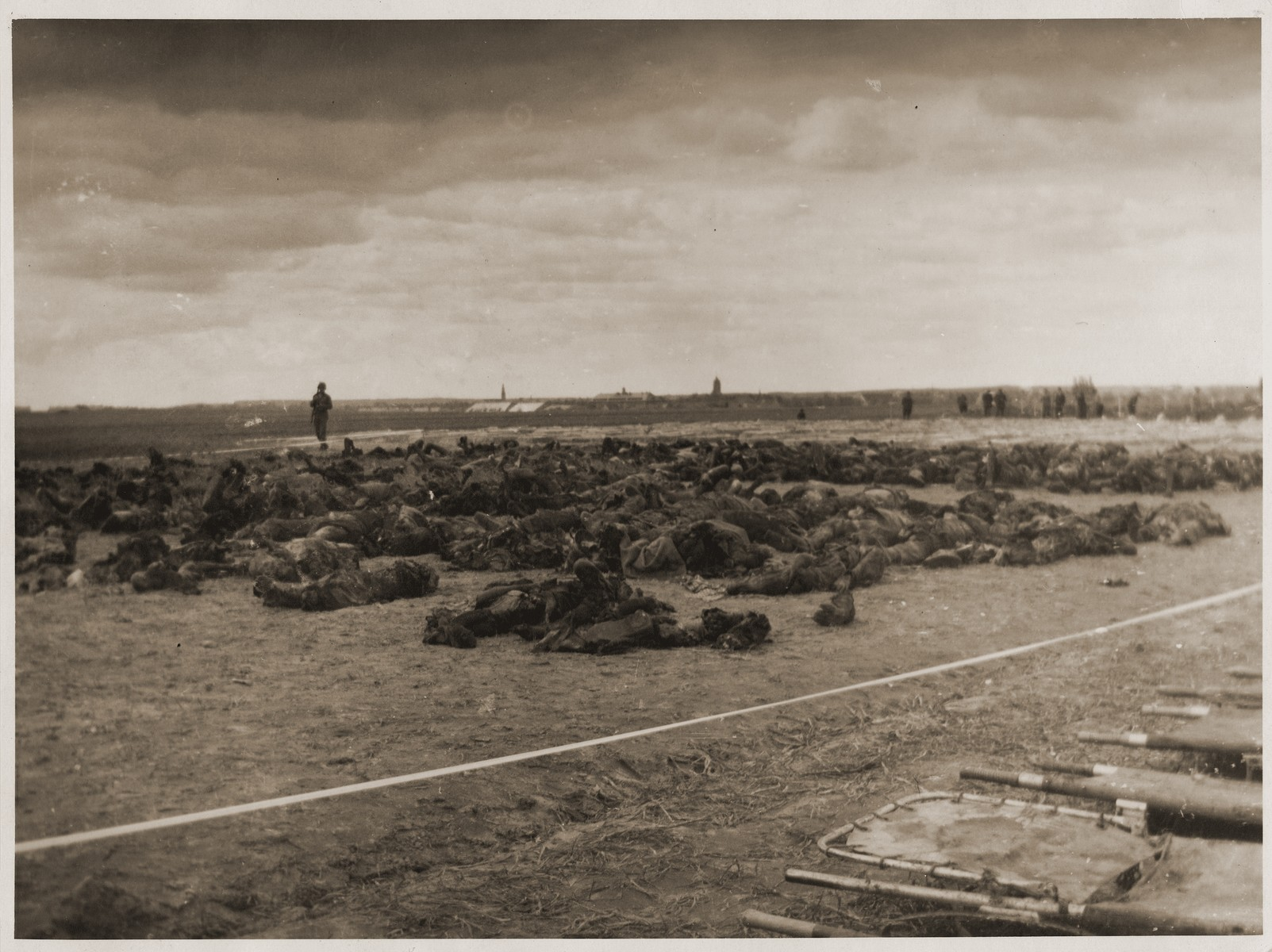 An American soldier looks at the bodies of concentration camp prisoners killed by the SS in a barn just outside of Gardelegen.  In the background, Germans prepare mass graves in which to bury the victims.