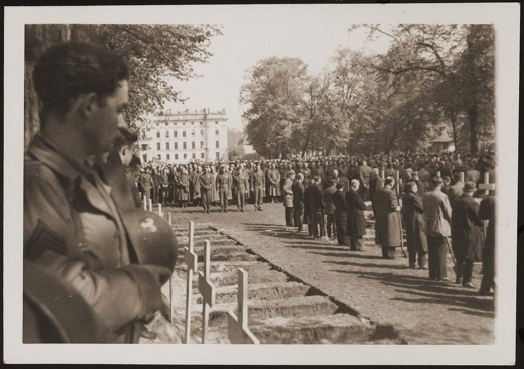 German civilians from Ludwigslust pause for a moment of silence at the mass funeral on the palace grounds of the Archduke of Mecklenburg, where they were forced by U.S. troops to bury the corpses of prisoners killed in the Woebbelin concentration camp.  The ram insignia on the helmet of the American soldier in the foreground indicates that he was a member of the 348th Engineer Combat Battalion.