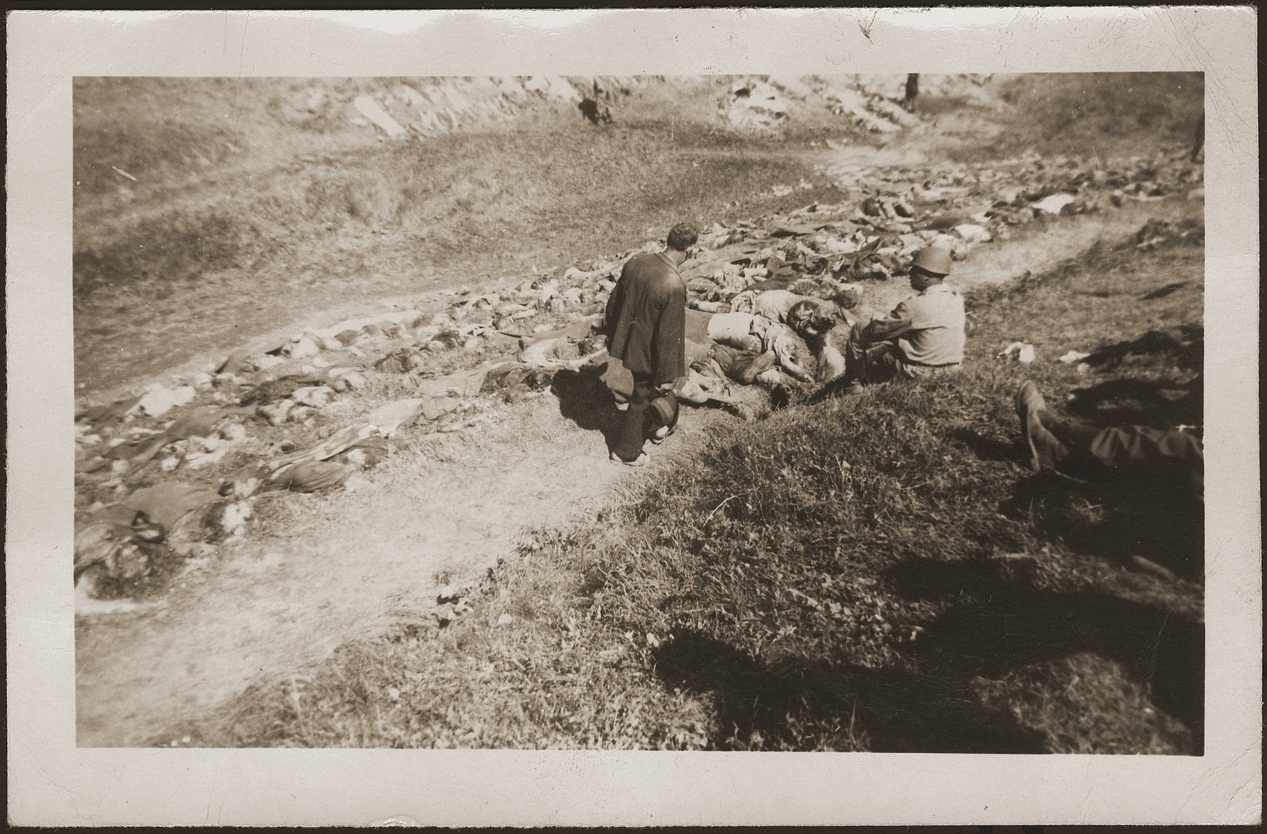 A German civilian from Nammering looks at the corpses of prisoners exhumed from a mass grave near the town.