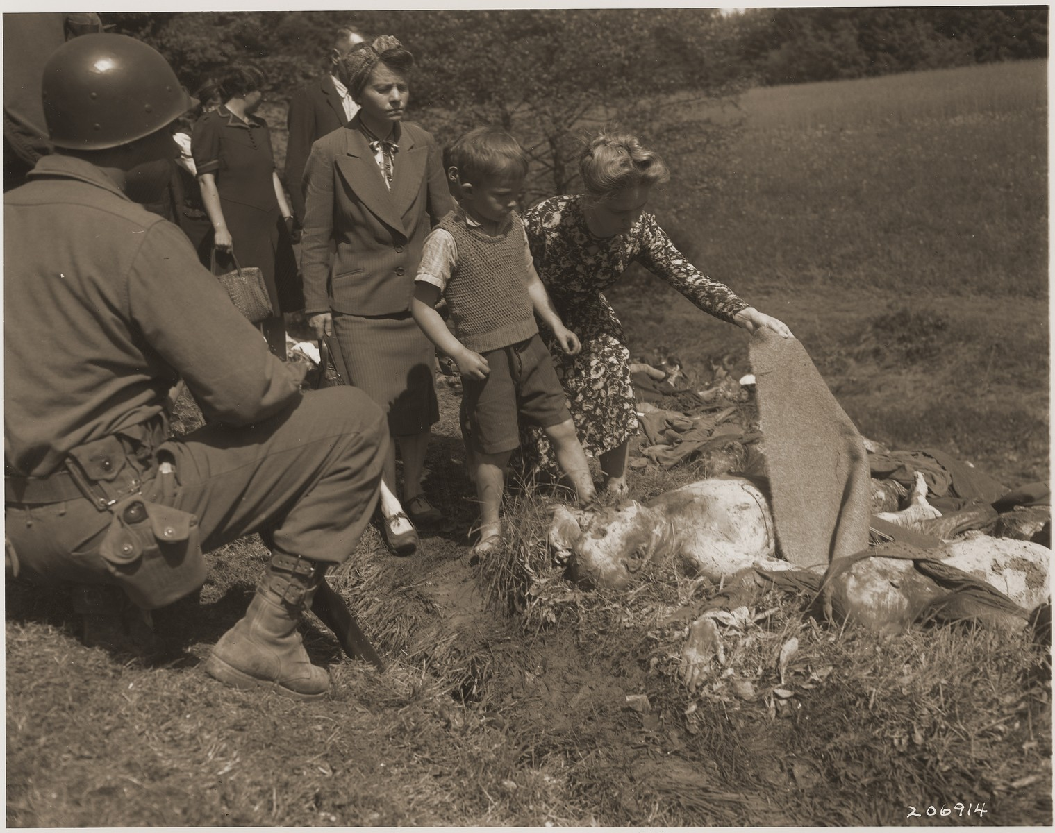 German civilians are forced to see the bodies of prisoners exhumed from a mass grave near Nammering.    An African- American soldier observes the procession of German civilians.