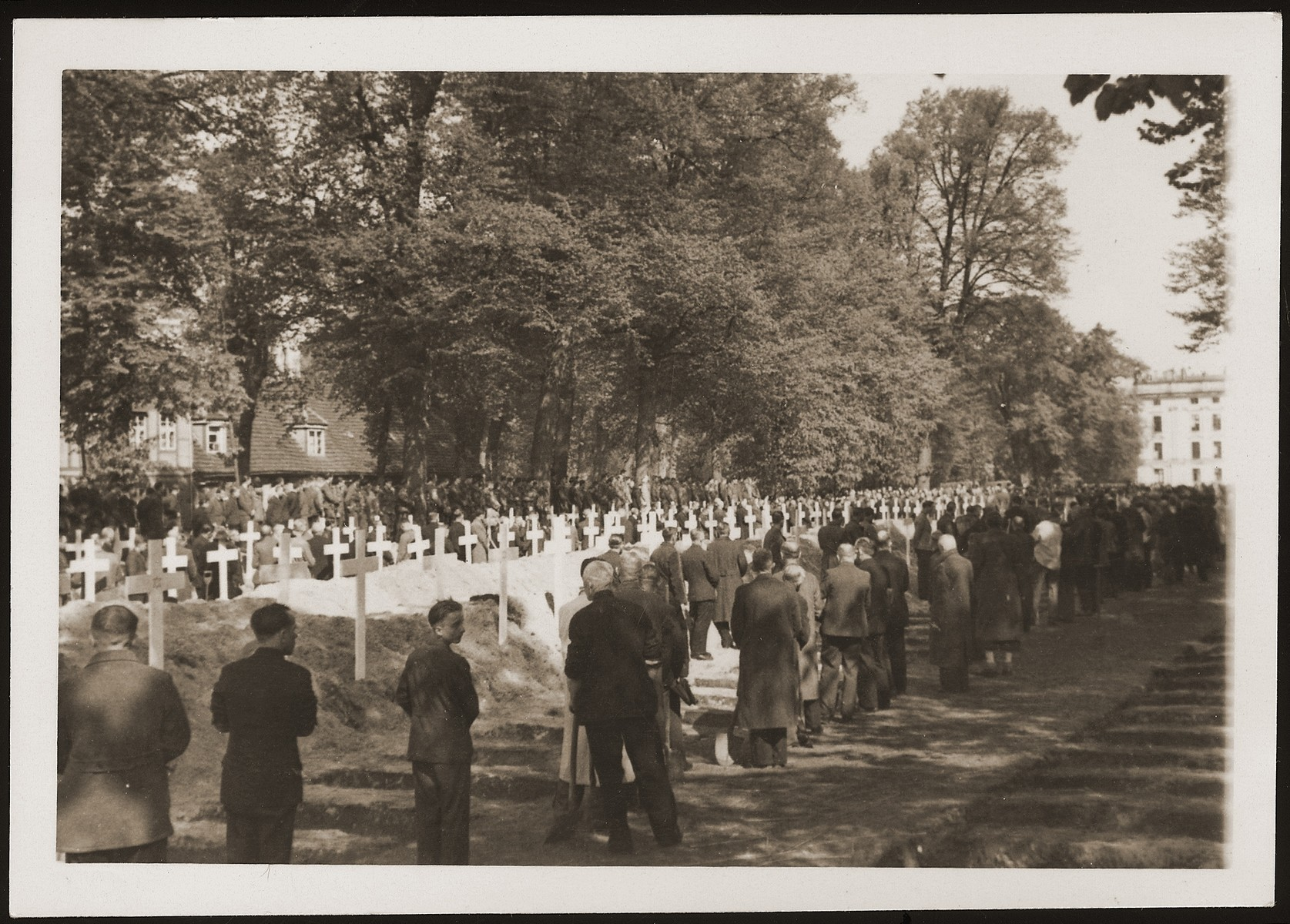 German civilians from Ludwigslust pause for a moment of silence at the mass funeral on the palace grounds of the Archduke of Mecklenburg, where they have been forced by U.S. troops to bury the bodies of prisoners killed in the Woebbelin concentration camp.