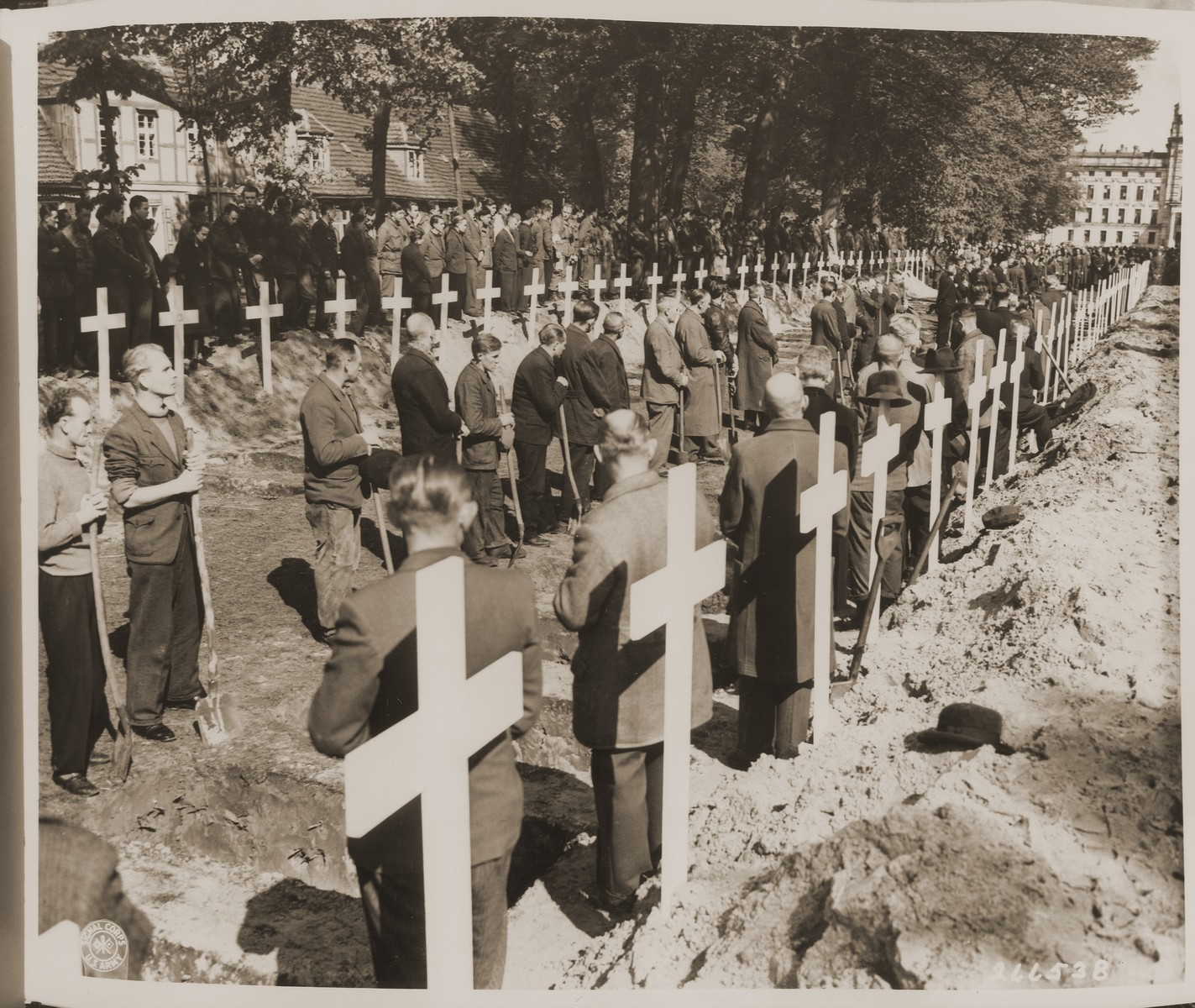 German civilians pause for a moment of silence at the mass funeral on the palace grounds of the Archduke of Mecklenburg in Ludwigslust, where the townspeople were forced by U.S. troops to bury the bodies of prisoners killed in the Woebbelin concentration camp.