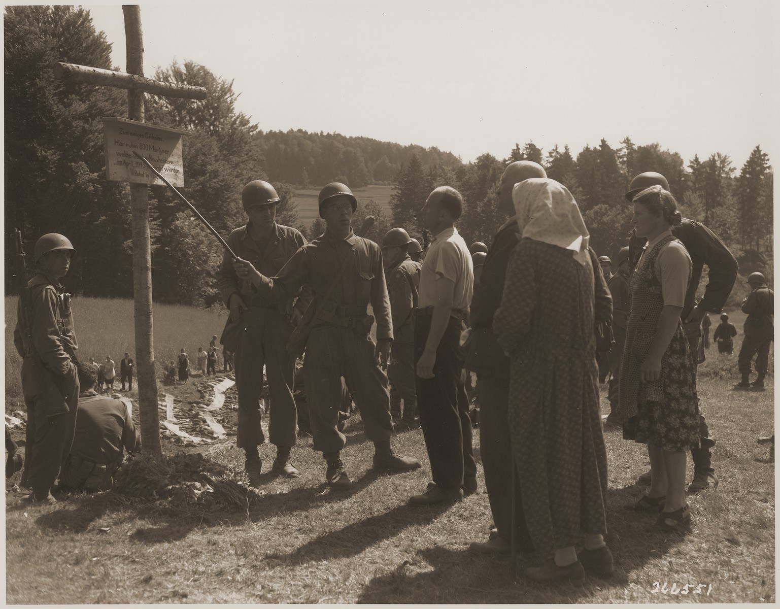 An American soldier points out a sign to German civilians that memorializes the 800 prisoners shot by the SS near the town of Nammering.  In the background, other German civilians walk among corpses exhumed from the mass grave.