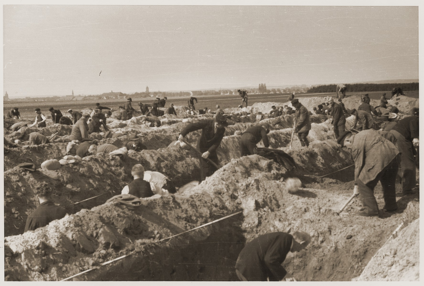 German civilians dig graves for the bodies of concentration camp prisoners killed by the SS in a barn just outside of Gardelegen.  The town of Gardelegen can be seen in the distance.