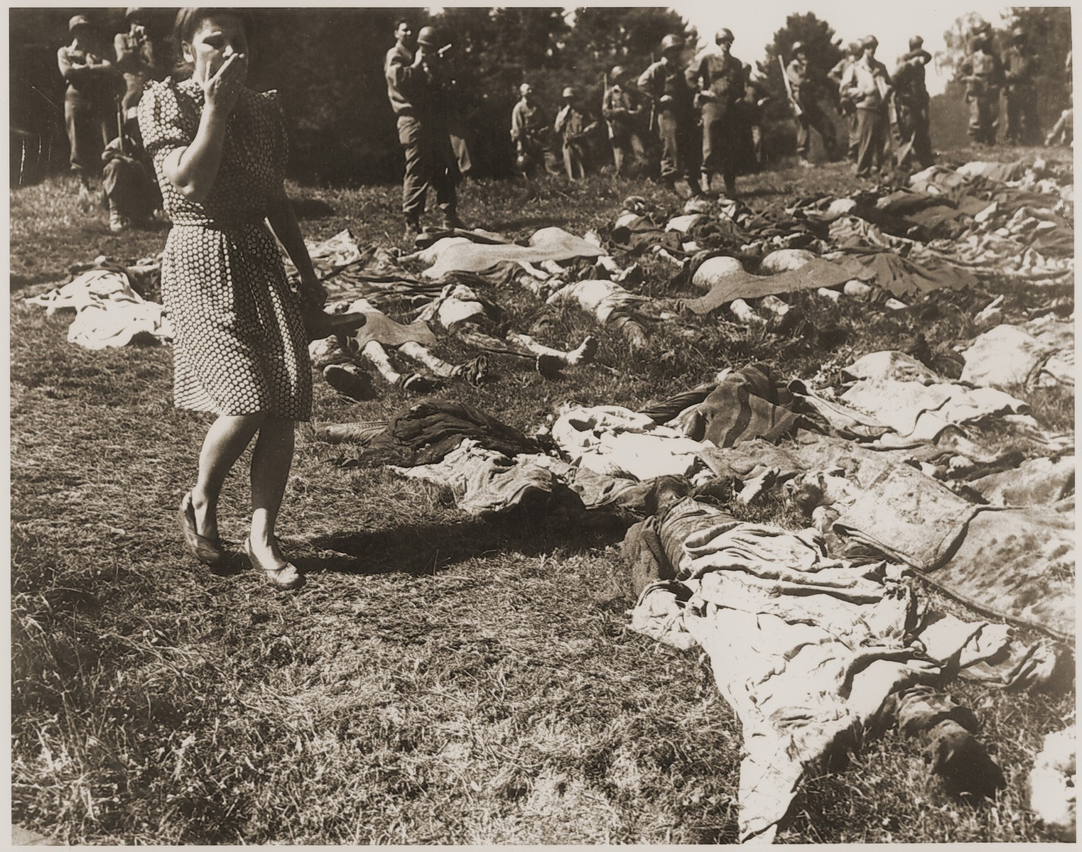 Under the supervision of American troops, a German woman is forced to walk among the corpses of prisoners exhumed from a mass grave near Nammering.