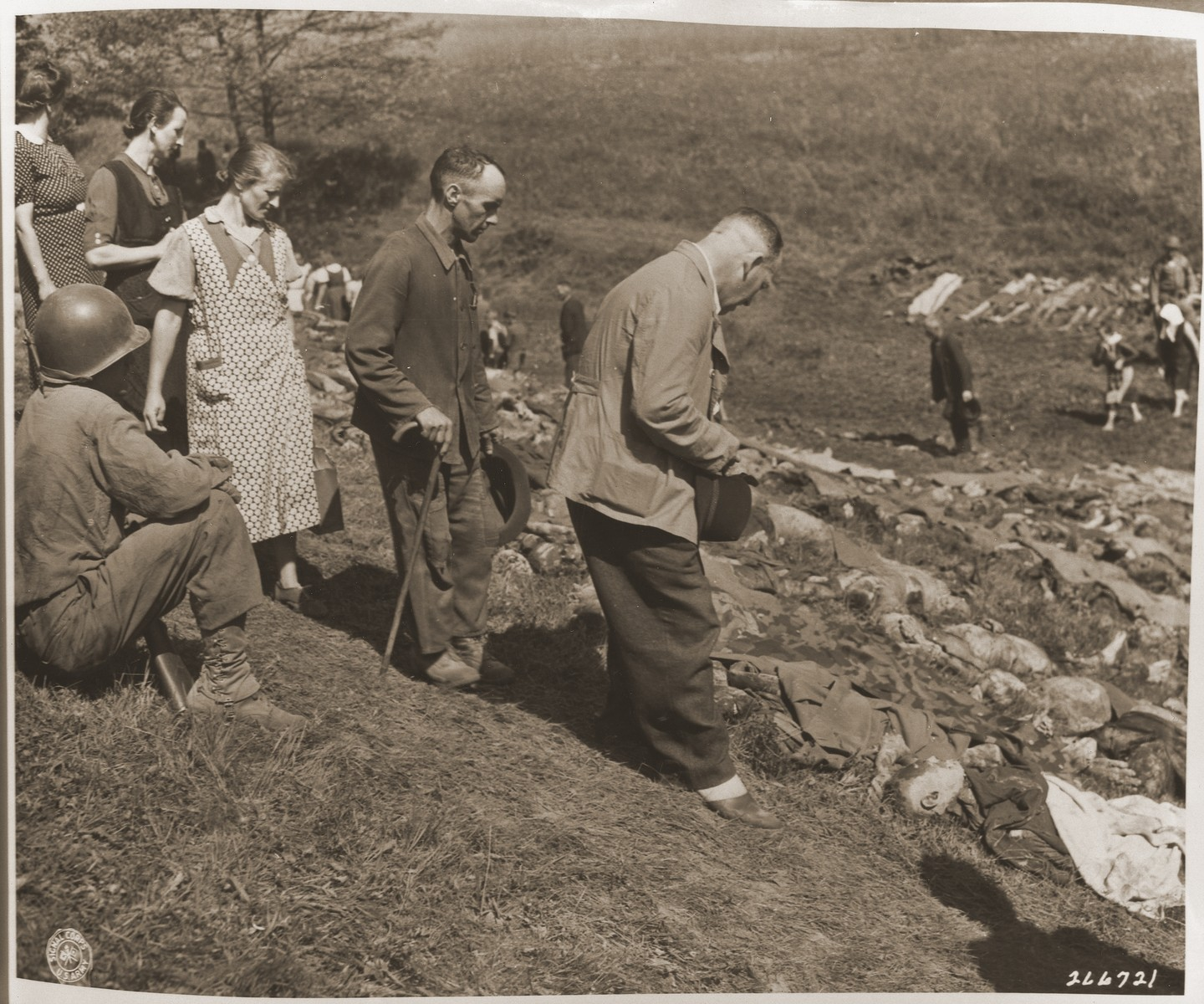 Under the supervision of American soldiers, German civilians from Nammering are forced to look at the corpses of prisoners exhumed from a mass grave near the town.