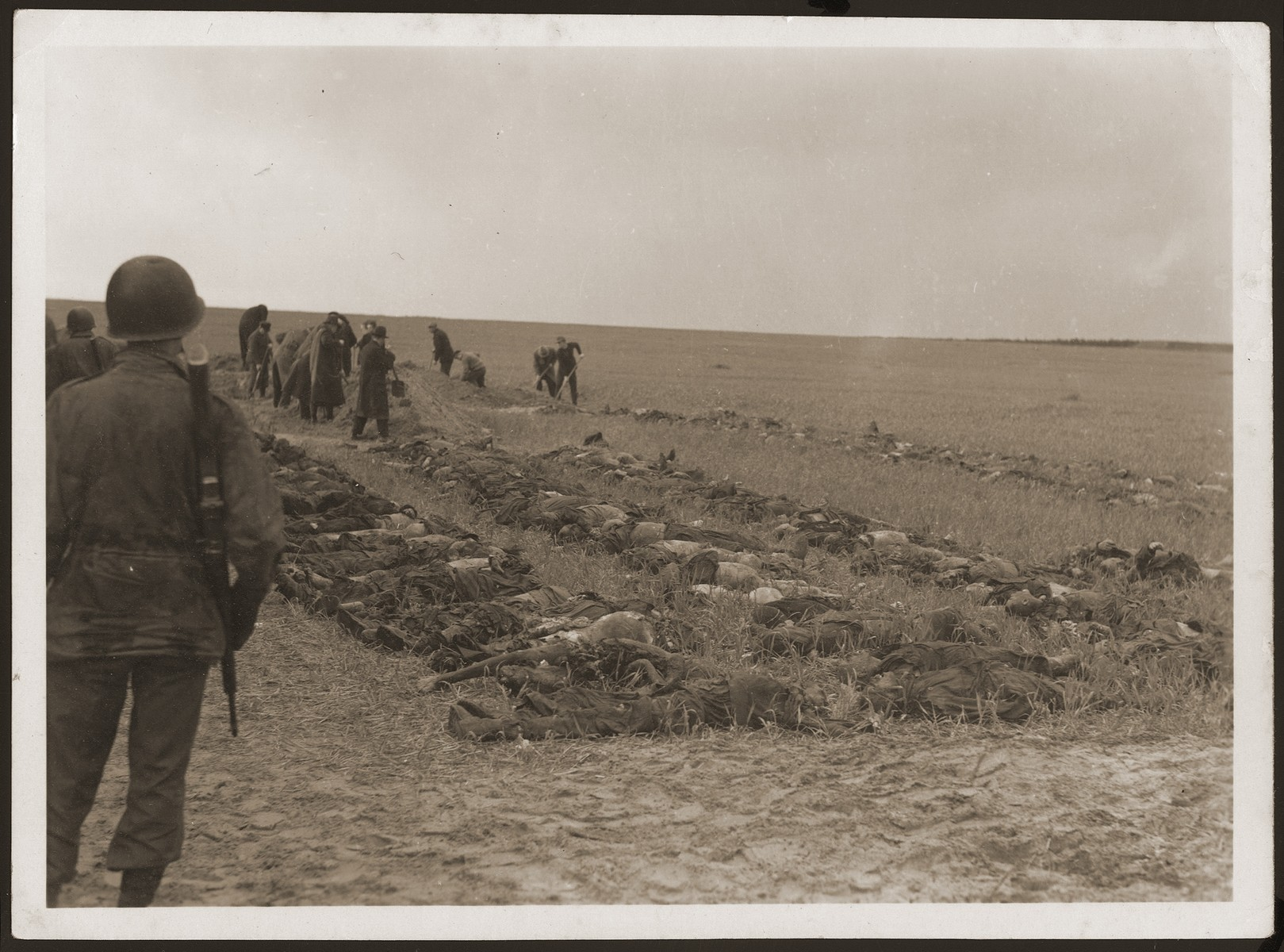 Under the supervision of American soldiers, German civilians from Gardelegen dig graves for the bodies of prisoners killed by the SS in a barn just outside the town.