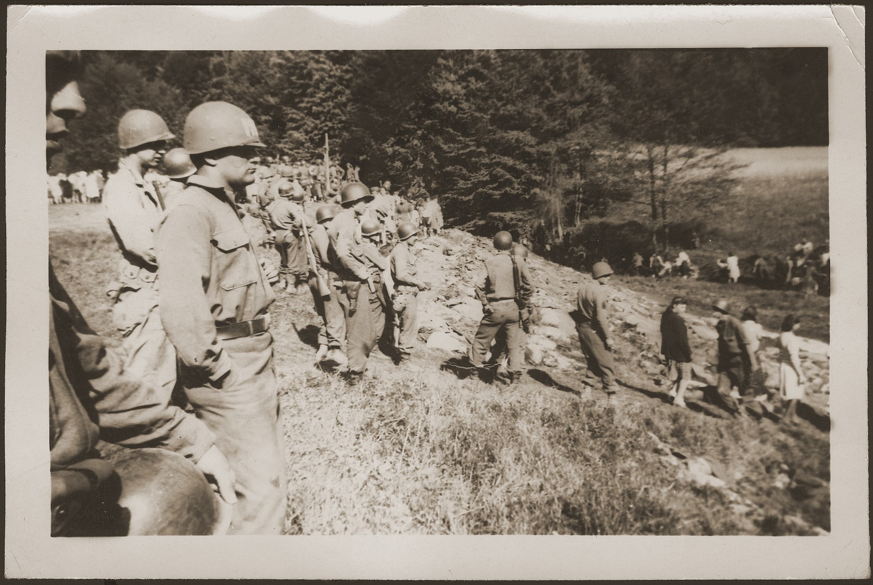 Under the supervision of American soldiers, German civilians from Nammering look at the corpses of prisoners exhumed from a mass grave near the town.