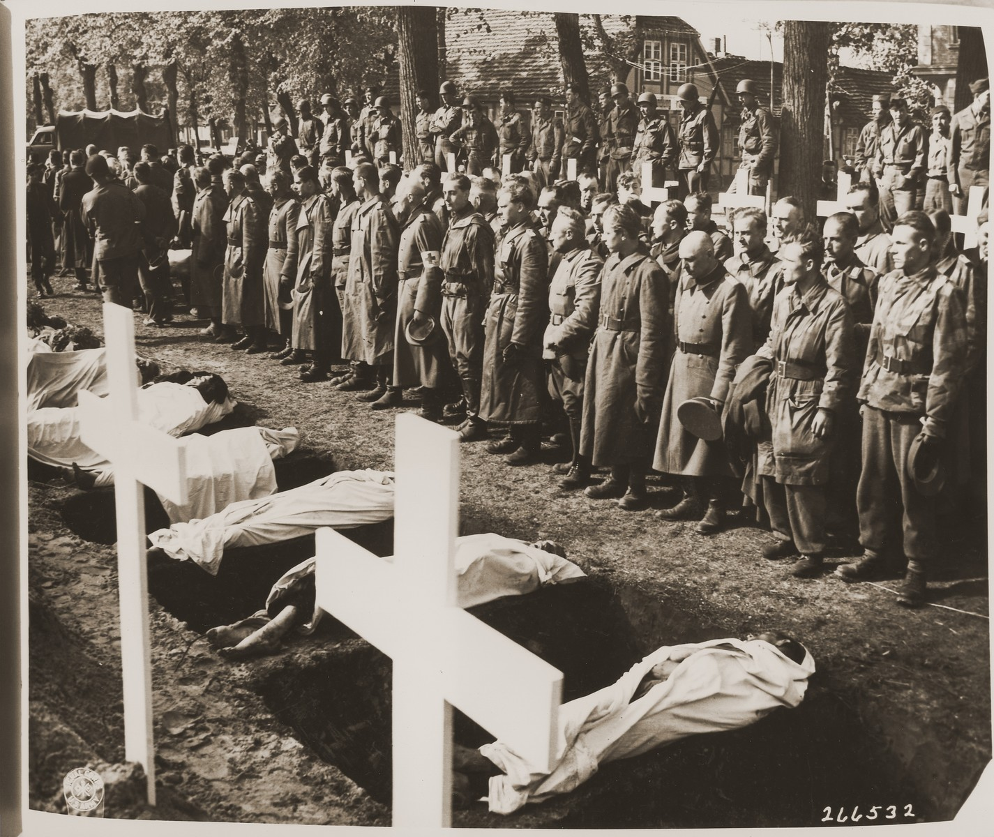 "German soldiers pause for a moment of silence at the mass funeral on the palace grounds of the Archduke of Mecklenburg in Ludwigslust, where the townspeople were forced by U.S. troops to bury the bodies of prisoners killed in the Woebbelin concentration camp.  The original Signal Corps caption (from copy from Ron Leidelmeyer) reads, ""NEW NAZI HORROR CAMP DISCOVERED.  One of the worst Nazi concentration camps uncovered by Allied troops was liberated at Wobbelin, Germany, a small town five miles north of Ludwigslust and 90 miles northwest of Berlin.  Soldiers of three Allied units -- the 82nd U.S. Airborne Division, the Eighth Infantry Division of the Ninth U.S. Army and airborne troops of the Second British Army -- entered the camp and found sick, starving inmates barely surviving under indescribable conditions of filth and squalor.  They found hundreds of dead prisoners in one of the buildings while outside, in a yard, hundreds more  were found hastily buried in huge pits.  One mass grave contained 300 emaciated, disfigured corpses.  The dead included Poles, Russians, Frenchmen, Belgians, Dutchmen and Germans, all of whom had been working as slave laborers for the Nazis.  It is estimated that at least 150 of the original 4,000 prisoners succumbed daily, mostly from starvation and savage treatment at the hands of Nazi SS troops who operated the camp.   Some of the bodies found were burned almost beyond recognition and systematic torture of the inmates was revealed by the  physical condition of most of the survivors.  Military Government officers immediately ordered leading citizens of nearby Ludwigslust and other towns to march through the camp and witness the atrocities committed by representatives of the German Government.  Most of the civilians disclaimed any knowledge of the camp's existence despite the fact that many of the prisoners worked in the area.  The local residents later were made to exhume the bodies from the mass graves at the camp and provide decent, respectable interment of all dead prisoners.  Two hundred were buried in the public square of Ludwigslust May 7, 1945, and an equal number were buried in the garden of the highest Nazi official of Hagenow.  Eighty more were laid to rest in the town of Schwerin.  BIPPA                                                          EA 66633  THIS PHOTO SHOWS:  German soldiers stand bareheaded at the graves of these victims of German cruelty.  In the background, soldiers of the 82nd U.S. Airborne Division witness the burial proceedings at Ludwigslust.  U.S. Signal Corps Photo ETO-HQ-45-46088.   SERVICED BY LONDON OWI TO LIST B CERTIFIED AS PASSED  BY SHAEF CENSOR"