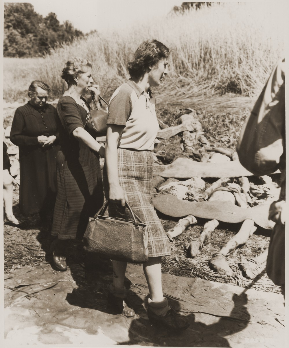 German women from Nammering are forced to walk among the corpses of prisoners exhumed from a mass grave.
