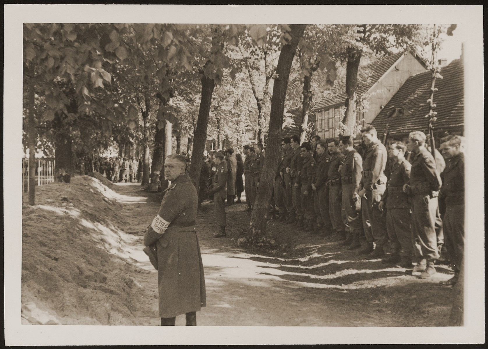 American soldiers and a German policeman observe a moment of silence at a mass funeral on the palace grounds of the Archduke of Mecklenburg, where the townspeople were forced by U.S. troops to bury the corpses of prisoners killed in the Woebbelin concentration camp .