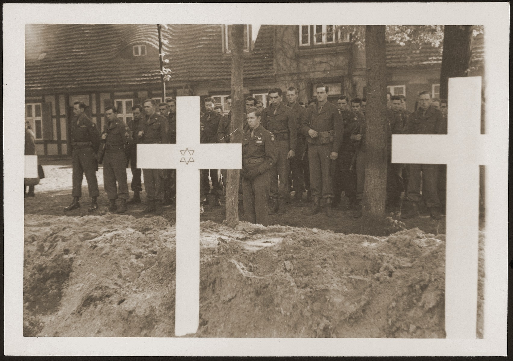 American soldiers observe a moment of silence at a mass funeral on the palace grounds of the Archduke of Mecklenburg, where they forced the townspeople to bury the corpses of prisoners killed in the Woebbelin concentration camp .