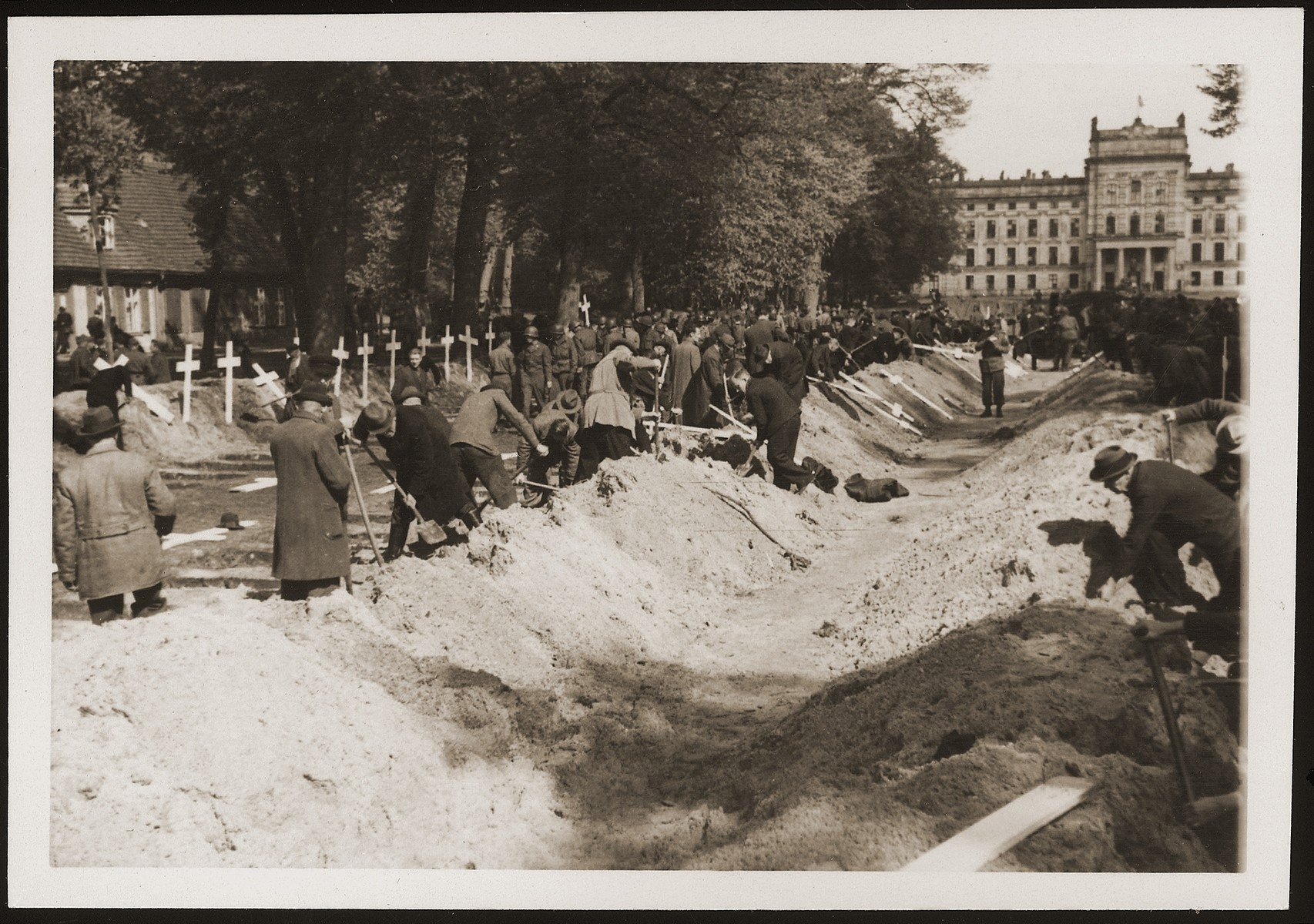 German civilians from Ludwigslust bury the corpses of prisoners killed in the Woebbelin concentration camp on the palace grounds of the Archduke of Mecklenburg.