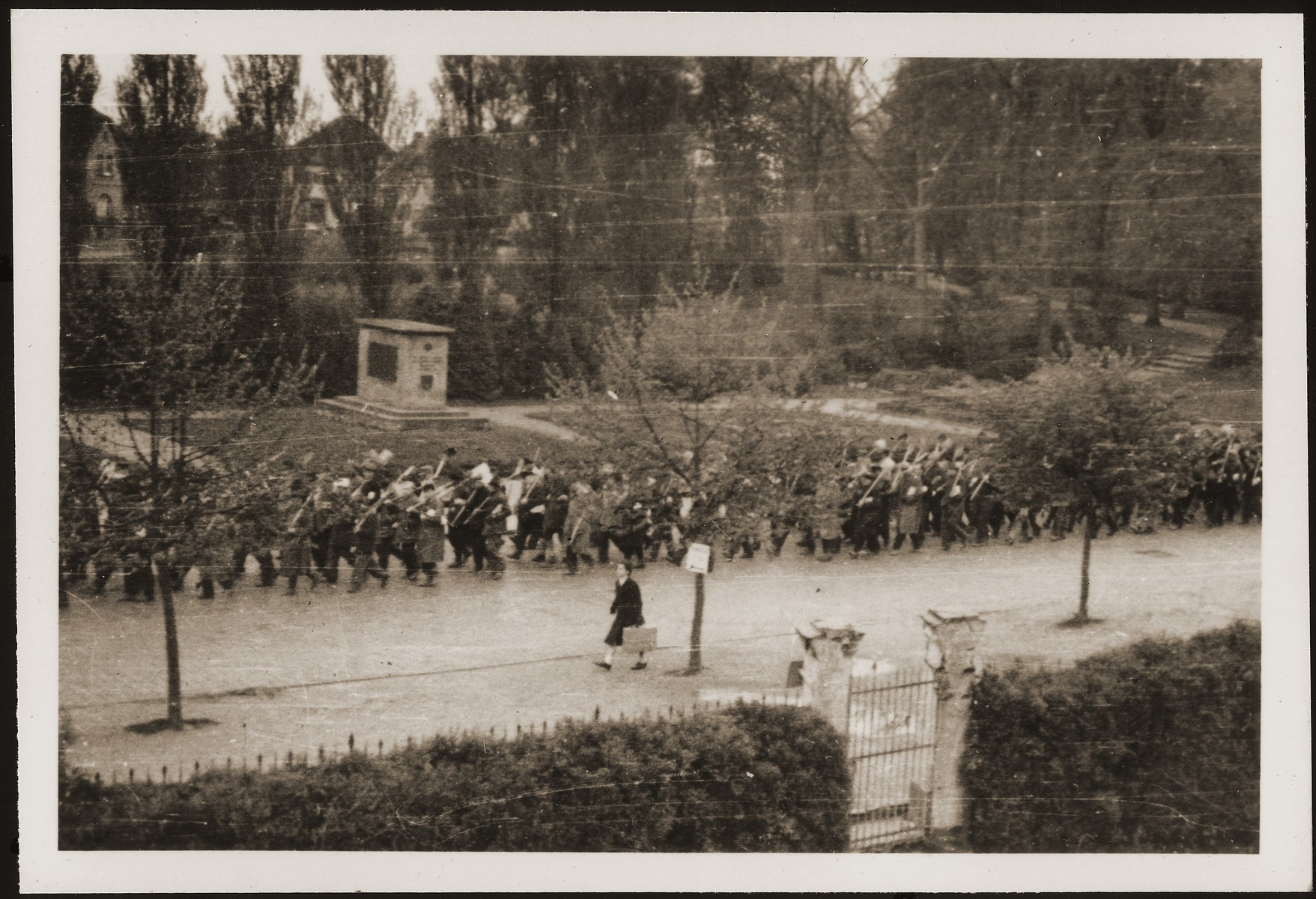 German civilians from Gardelegen march with shovels in hand to a barn just outside the town, where they will dig graves for prisoners killed by the SS inside the barn.