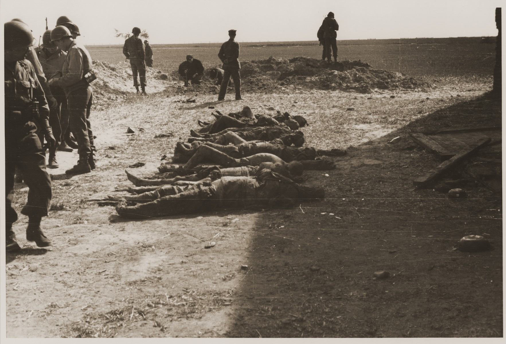 Under the supervision of American soldiers, German civilians exhume a mass grave containing the bodies of concentration camp prisoners killed by the SS in a barn outside Gardelegen.