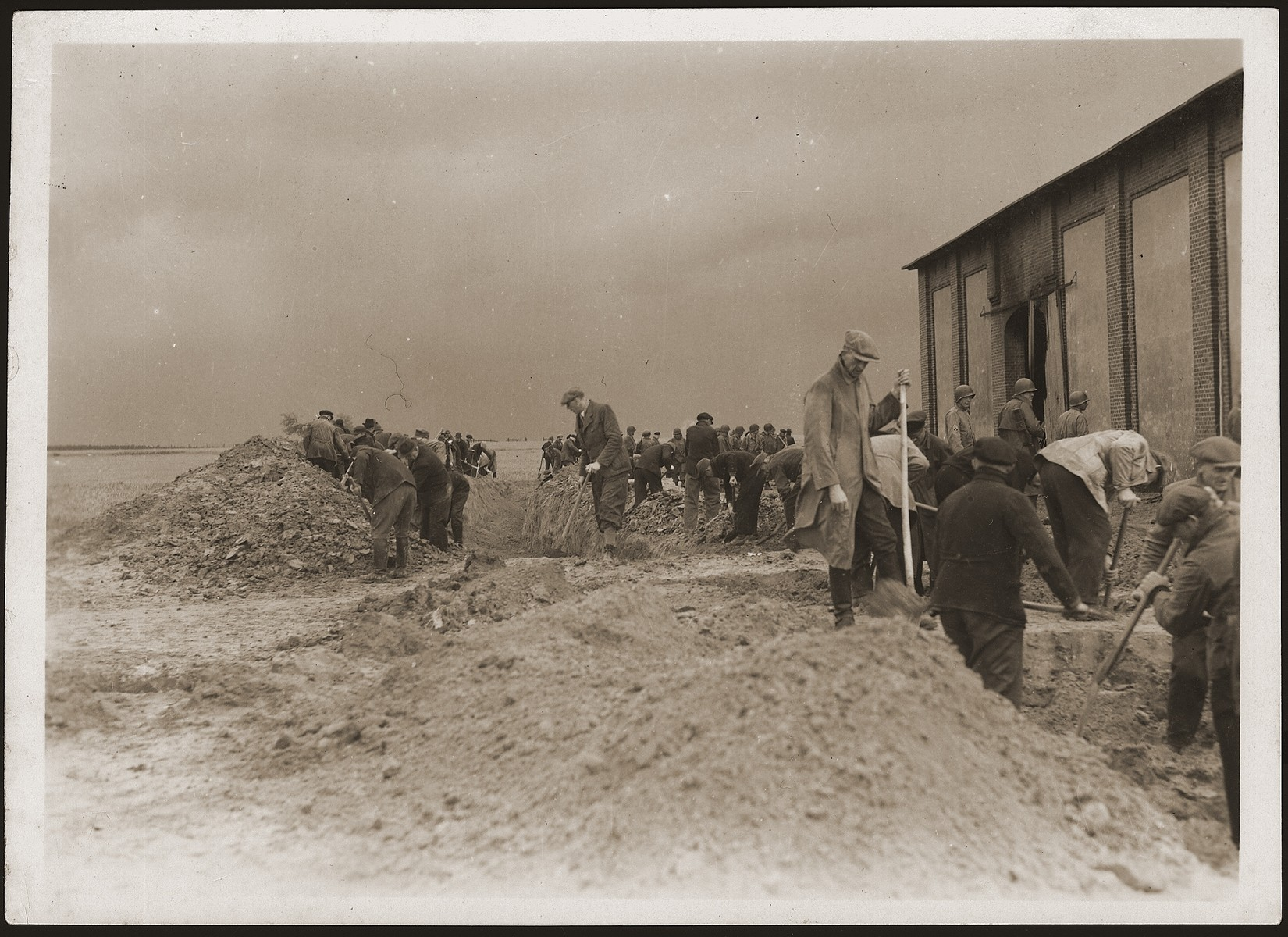 Under the supervision of American soldiers, German civilians exhume a mass grave containing the bodies of concentration camp prisoners killed by the SS in a barn just outside of Gardelegen.