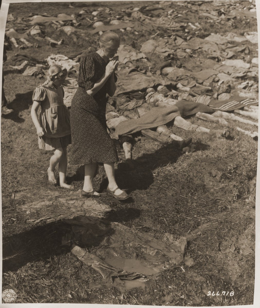 A German woman and a bare-footed young girl from Nammering are forced to walk among the corpses of prisoners exhumed from a mass grave near the town.