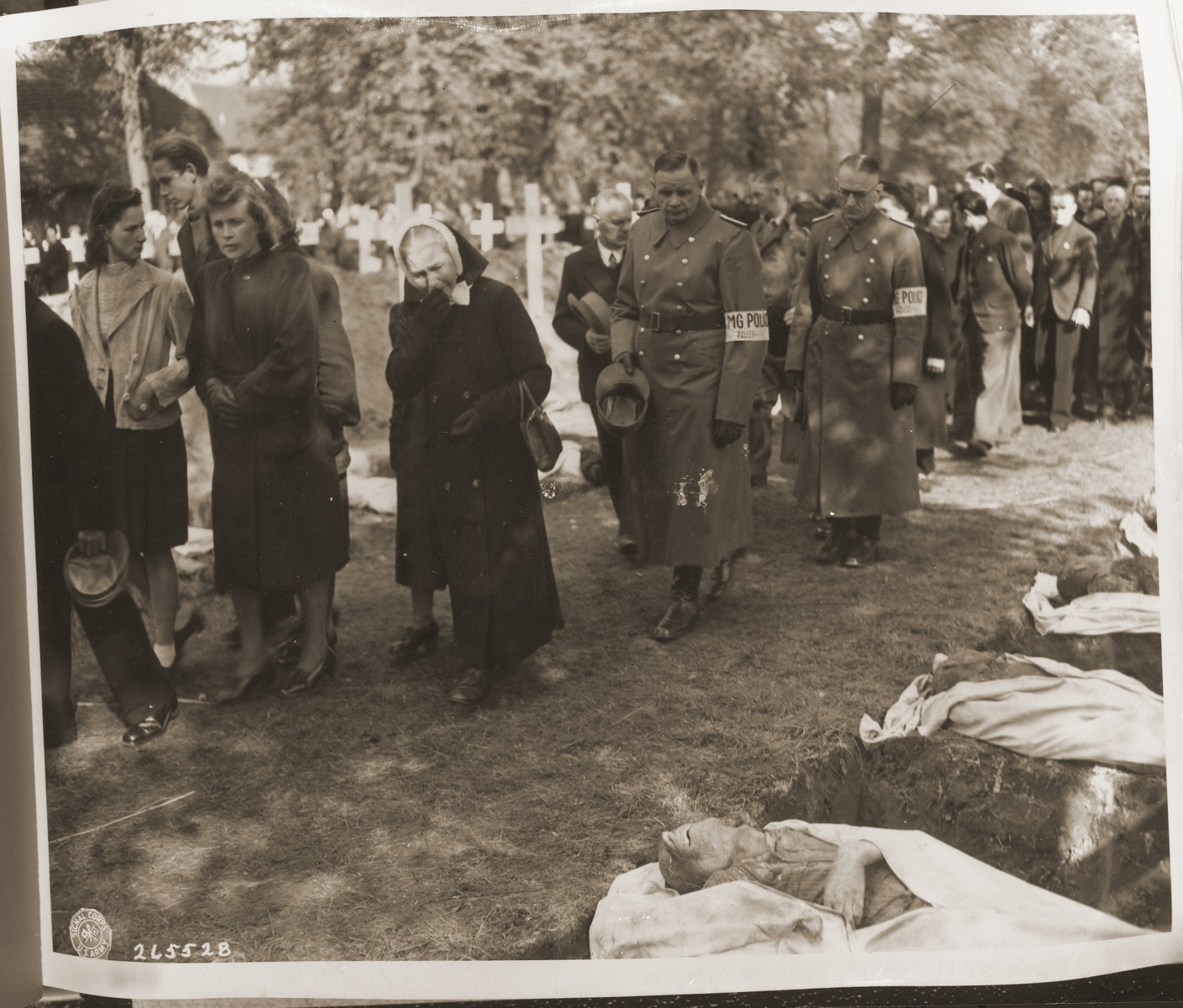 Civilians of all ages are forced to march past the open graves of victims from the concentration camp at Woebbelin.  The townspeople were forced by U.S. troops to bury the corpses on the palace grounds of the Archduke of Mecklenburg.