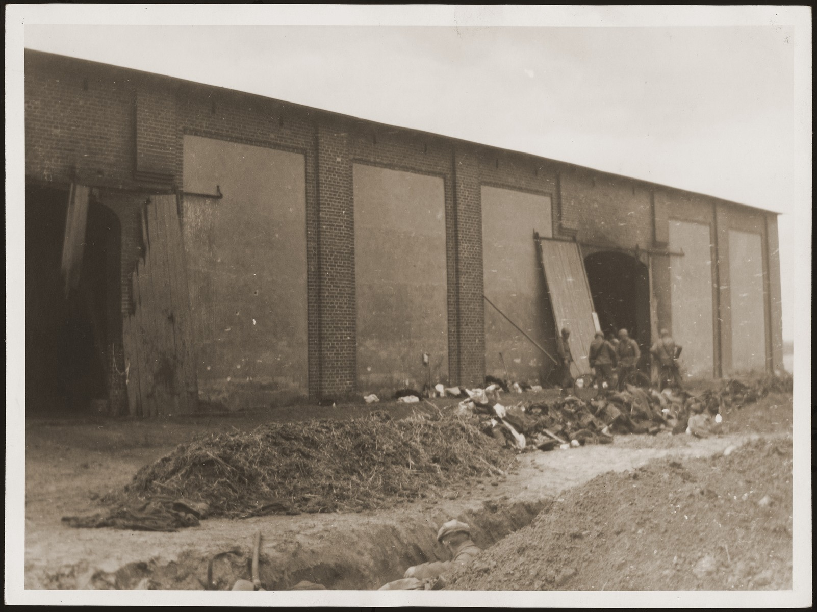 American soldiers stand in front of the barn in which concentration camp prisoners were burned alive by the SS.  German civilians exhume a mass grave in the foreground.