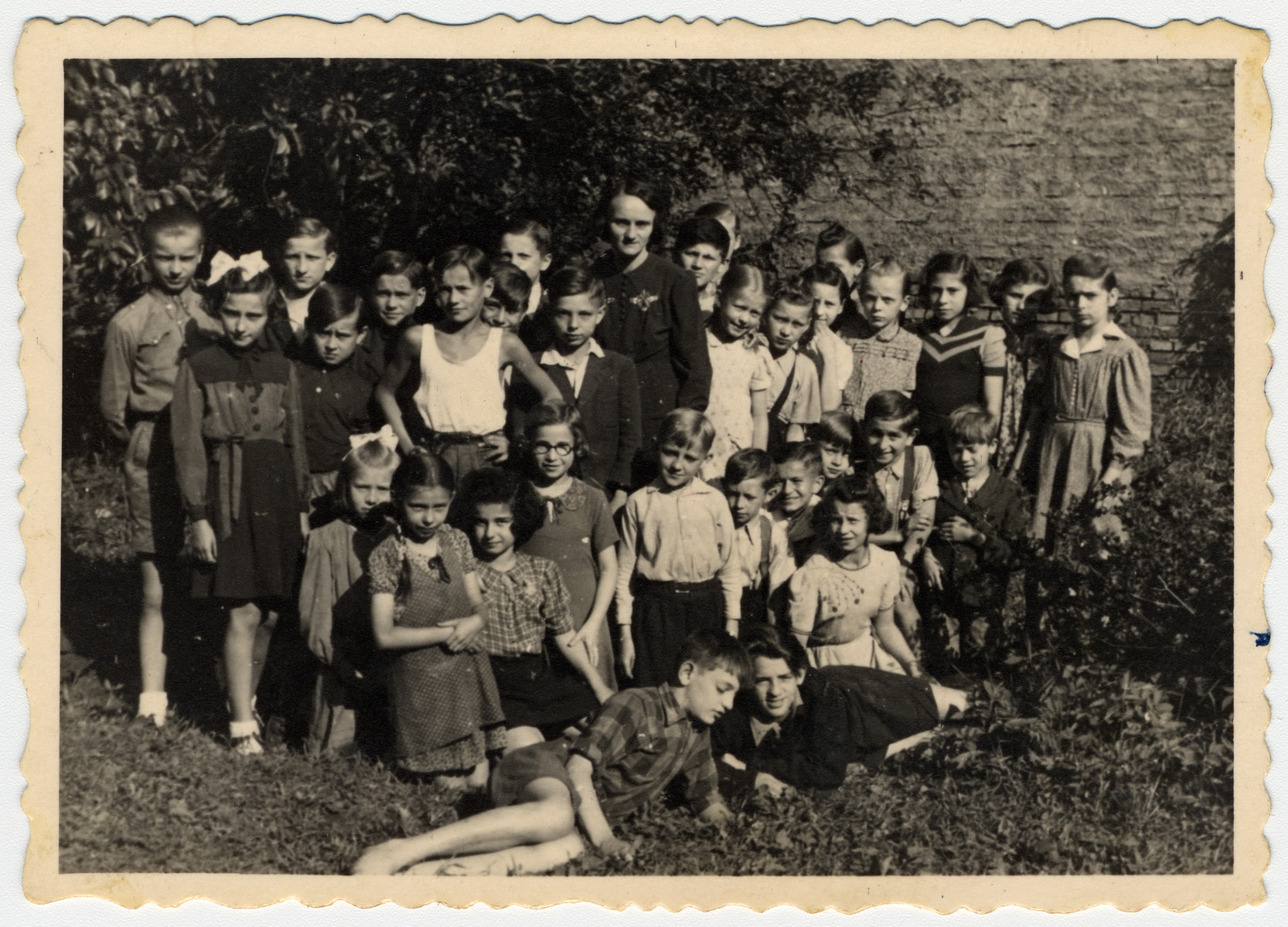 Group portrait of a fourth or fifth grade class in Bielsko Biala.  Among them are approximately eight Jewish orphans from a nearby children's home.  Among those pictured is Irena Ceder standing third from the right.