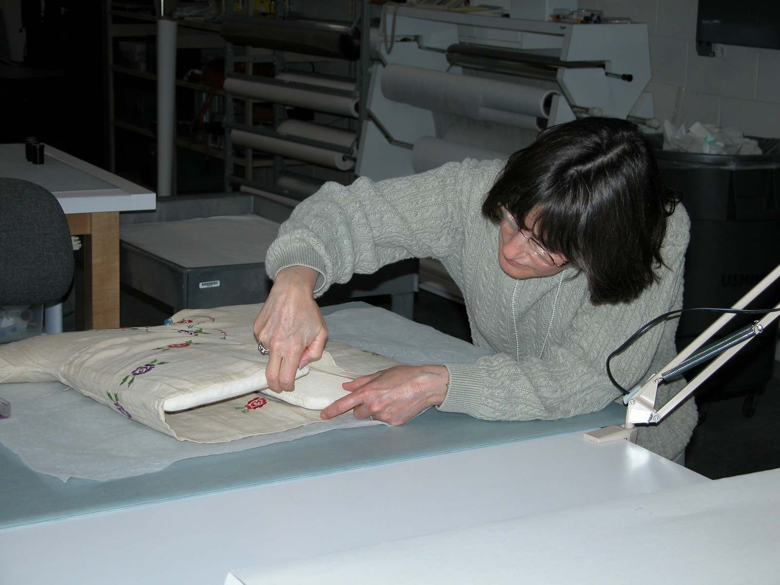 Textile conservator Gail Singer prepares a mount to display a dress worn by a Jewish child while living in hiding in Poland during World War II.  The dress was donated to the U.S. Holocaust Memorial Museum by its owner, Lola Kaufman.