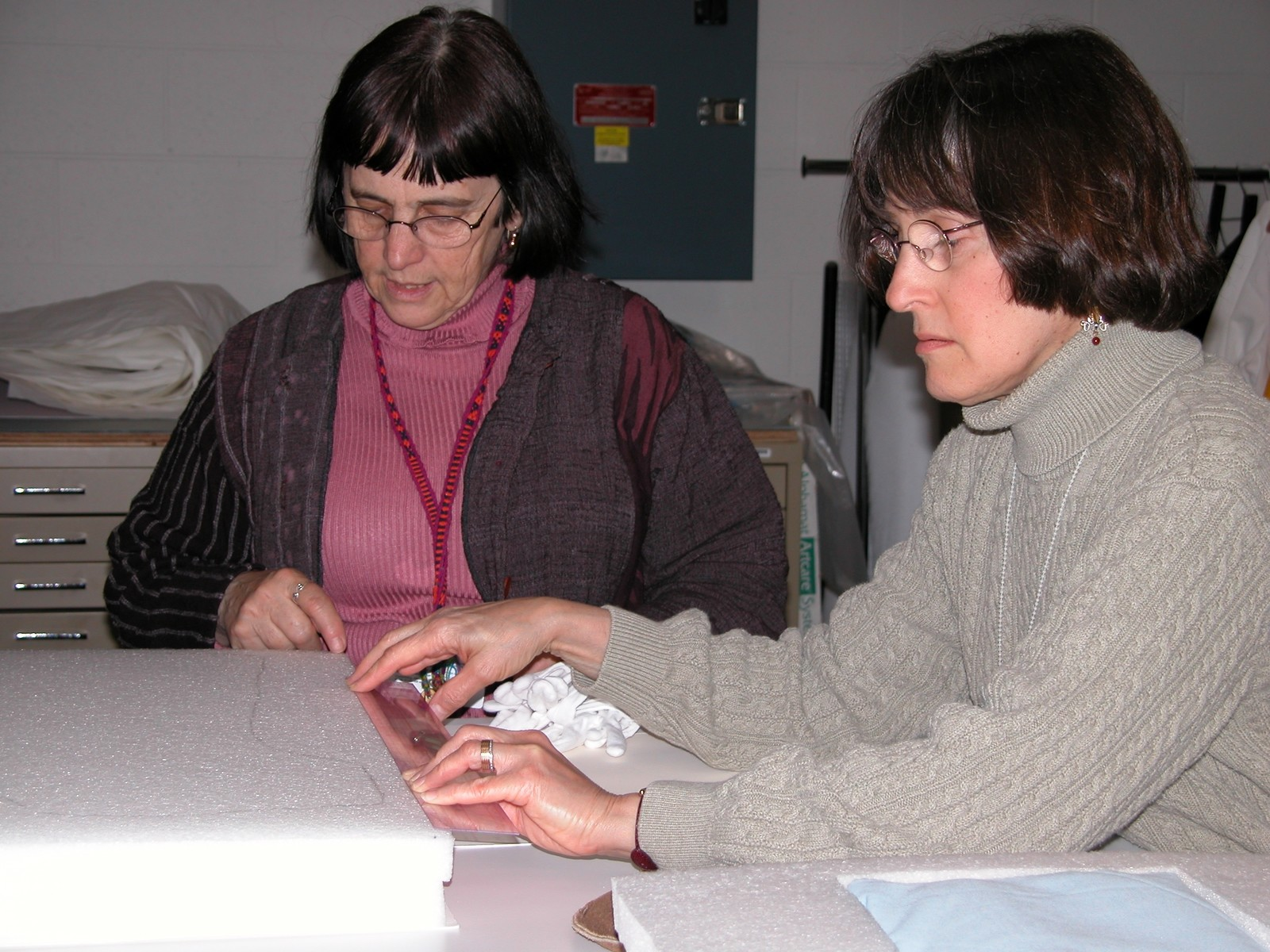 Textile conservators Lizou Fenyvesi and Gail Singer prepare a mount to display a dress worn by a Jewish child while living in hiding in Poland during World War II.  The dress was donated to the U.S. Holocaust Memorial Museum by its owner, Lola Kaufman.