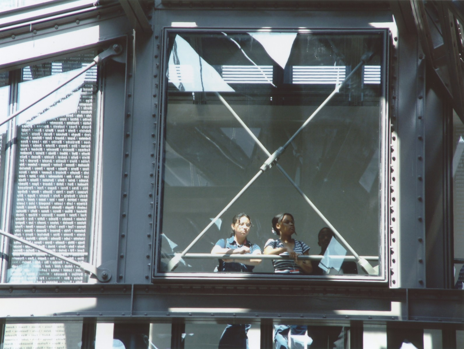 Two students look out from the third floor glass bridge in the permanent exhibition at the U.S. Holocaust Memorial Museum onto the Hall of Witness.