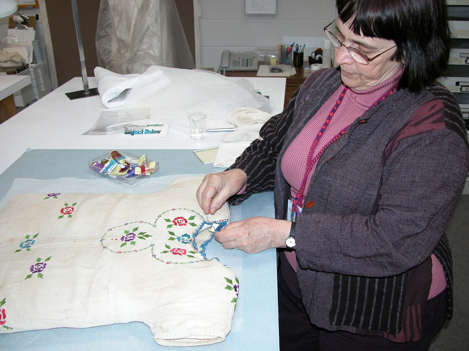 Textile conservator Lizou Fenyvesi repairs a dress worn by a Jewish child while living in hiding in Poland during World War II.  The dress was donated to the U.S. Holocaust Memorial Museum by its owner, Lola Kaufman.